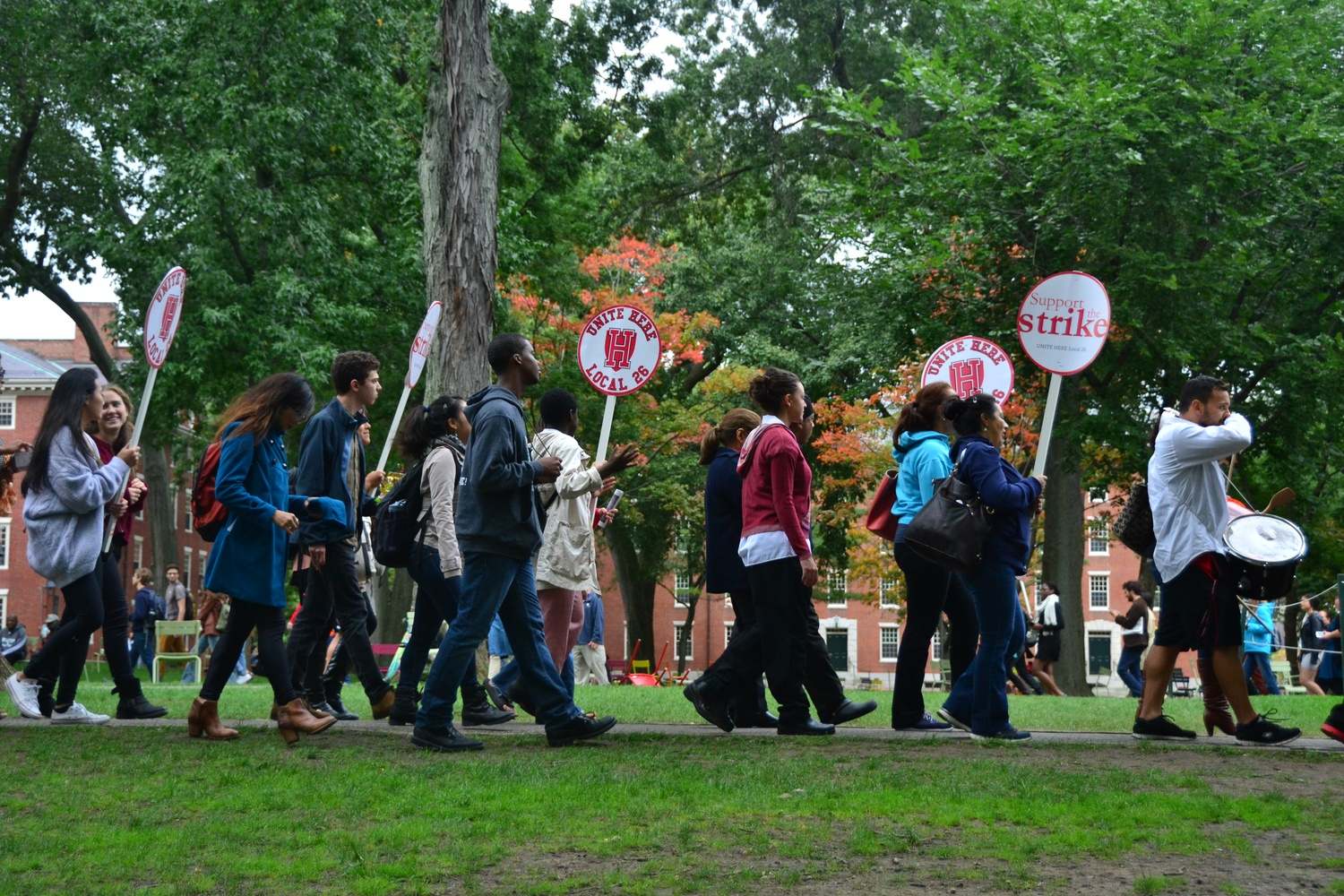 Harvard affiliates and HUDS workers circled Harvard Yard Friday afternoon, marching in support of the decision for HUDS workers to strike next Wednesday if the University does not comply with their requests.