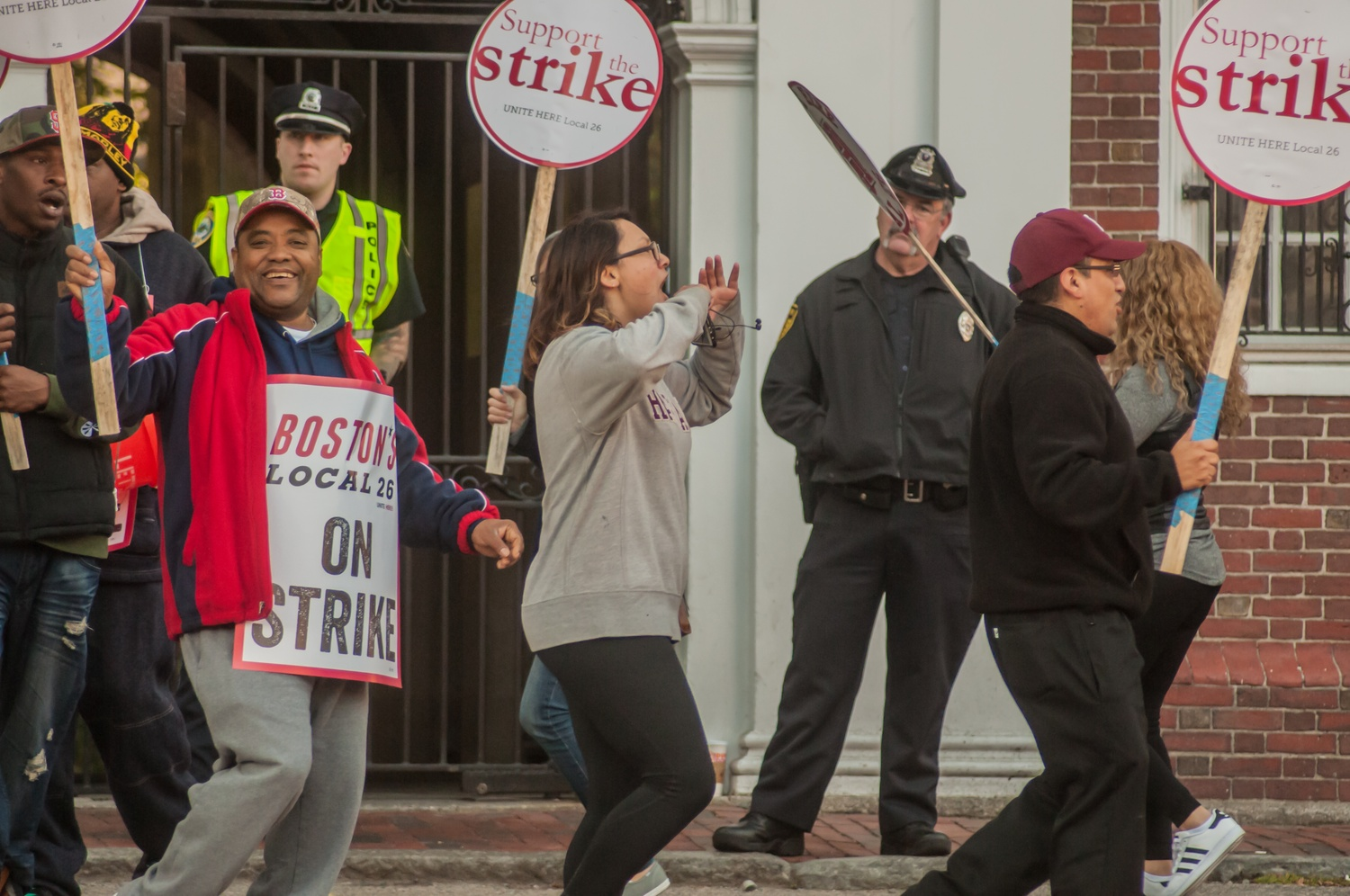 Camille E. Traslavina '18 marches with HUDS workers outside Lowell Wednesday morning.