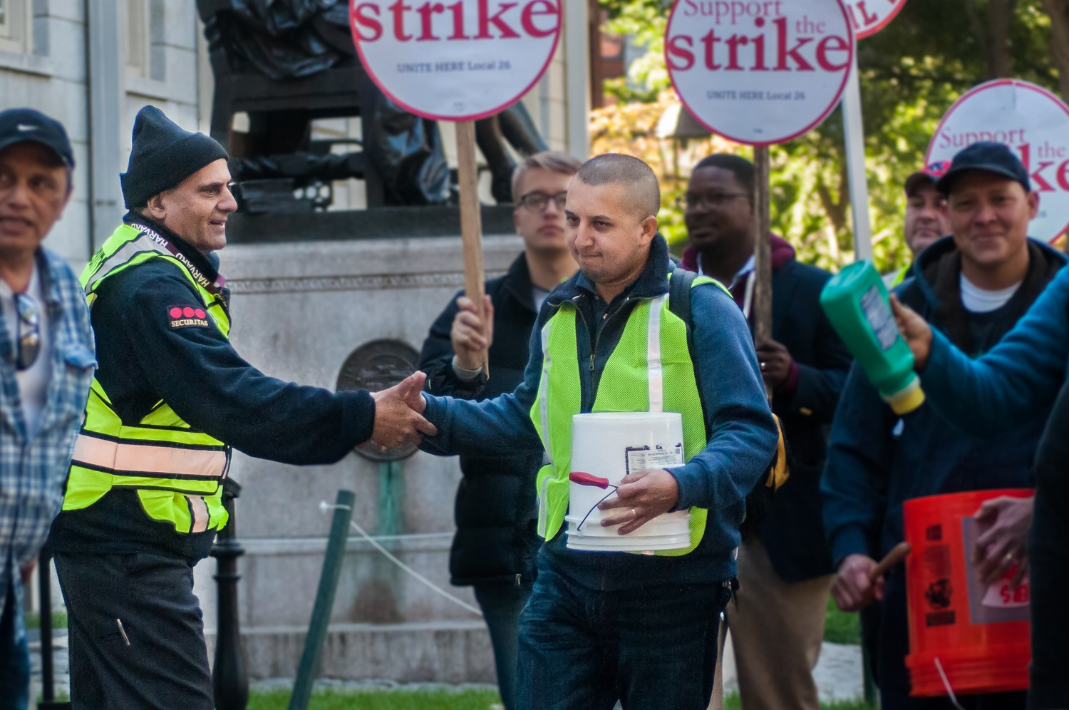 A security officer extends a handshake to one of the protestors during Wednesday morning's march through the yard. Police and security presence was especially high throughout the day.