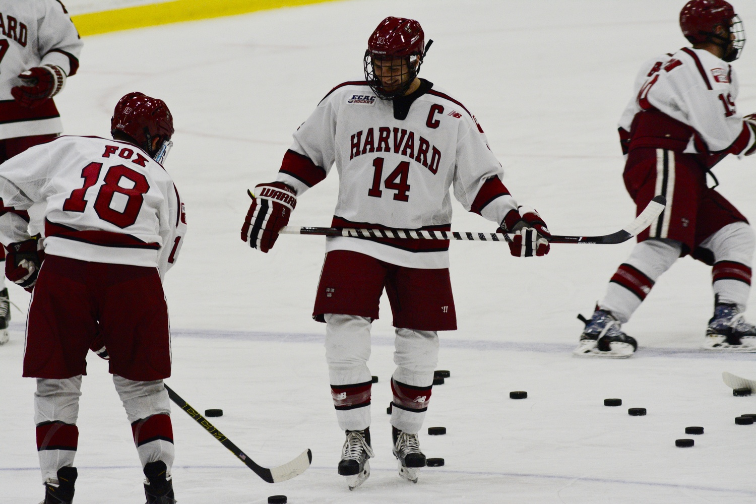 Adam Fox (18) and Alexander Kerfoot (14), shown during warmups, connected on Harvard's lone goal of the game Friday night.