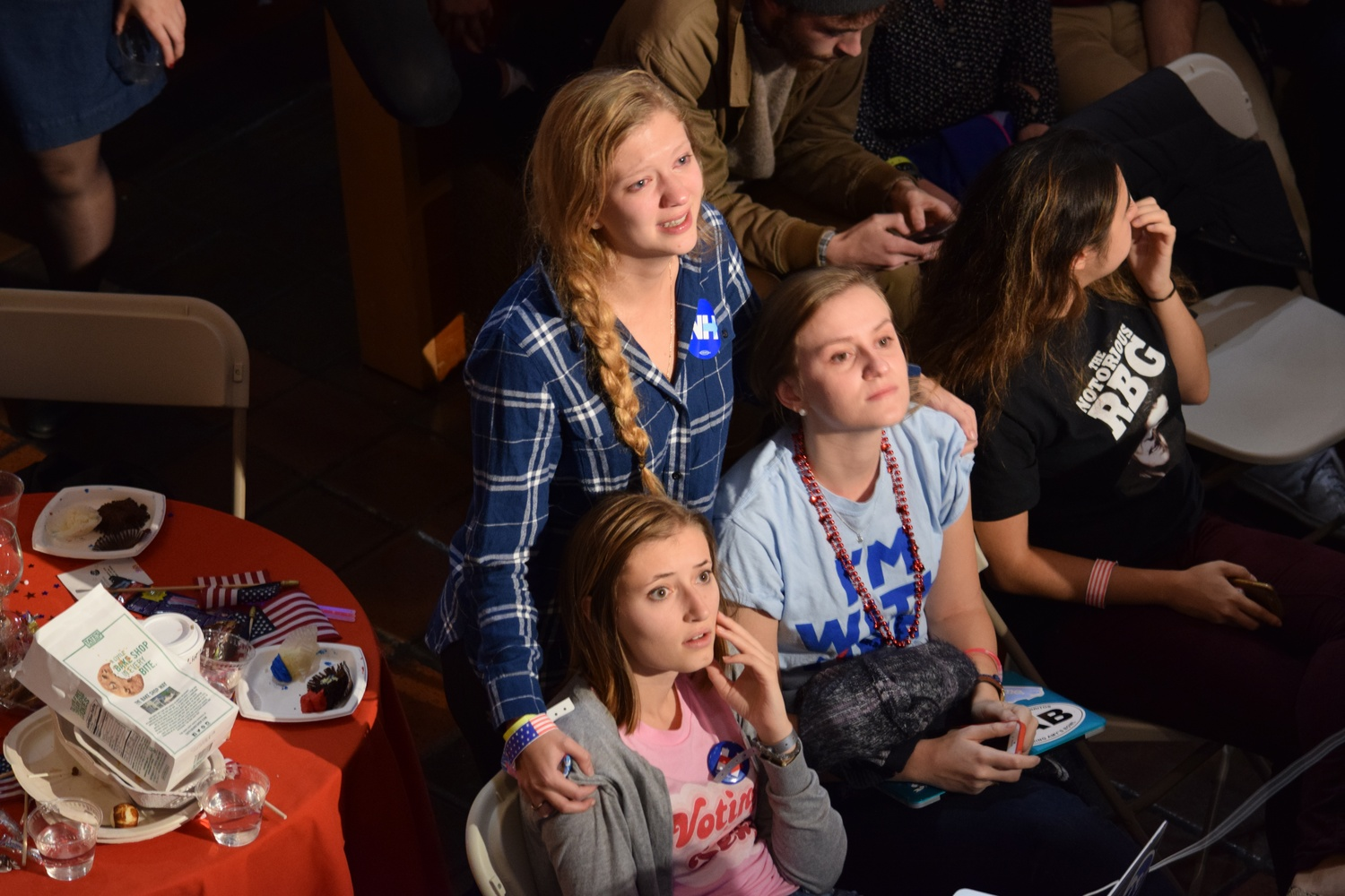 Caroline M. Tervo '18, Sally C. Marsh '18 and Megan K. Mers '17 comfort each other as the election results come in on Tuesday night at the IOP watch party.