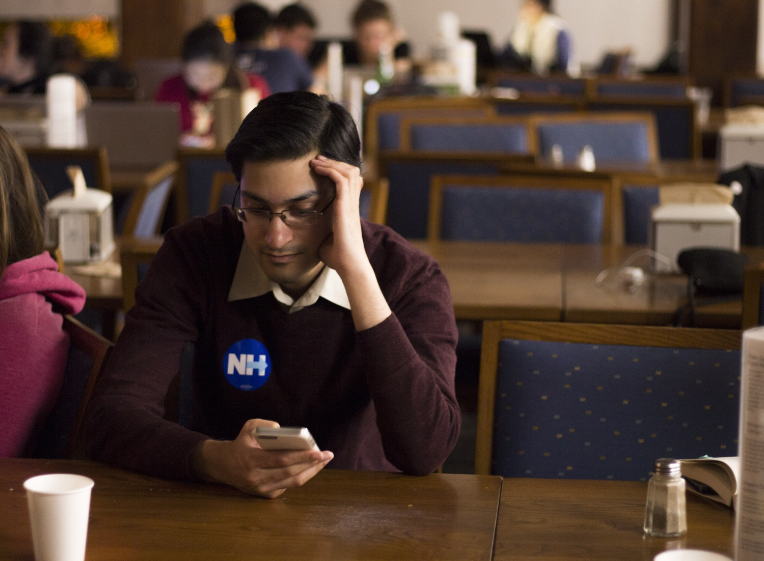 Rush Doshi, donning a Hillary Clinton sticker, checks his phone in despair shortly after the announcement of Donald Trump winning Ohio. Doshi attended the watch party in Quincy dining hall Tuesday night.