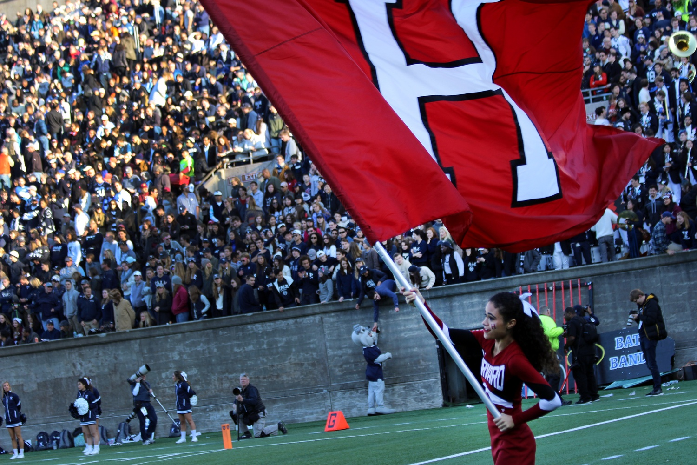 Cheerleader Camille N'Diaye-Muller '18 waves the Harvard flag during Saturday's game against Yale.