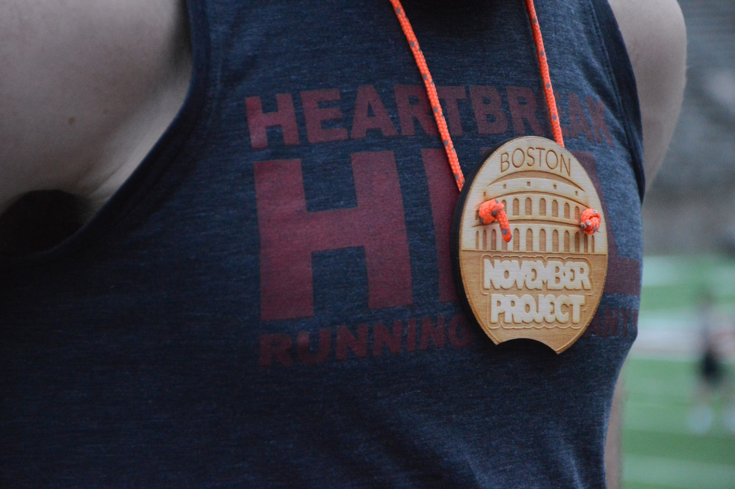 """Conor Hayden wears one of twelve """"NP High Five"""" medals.  According to Hayden, November Project participants pass the medals to other members """"as a way of recognizing someone who embodies what NP stands for."""