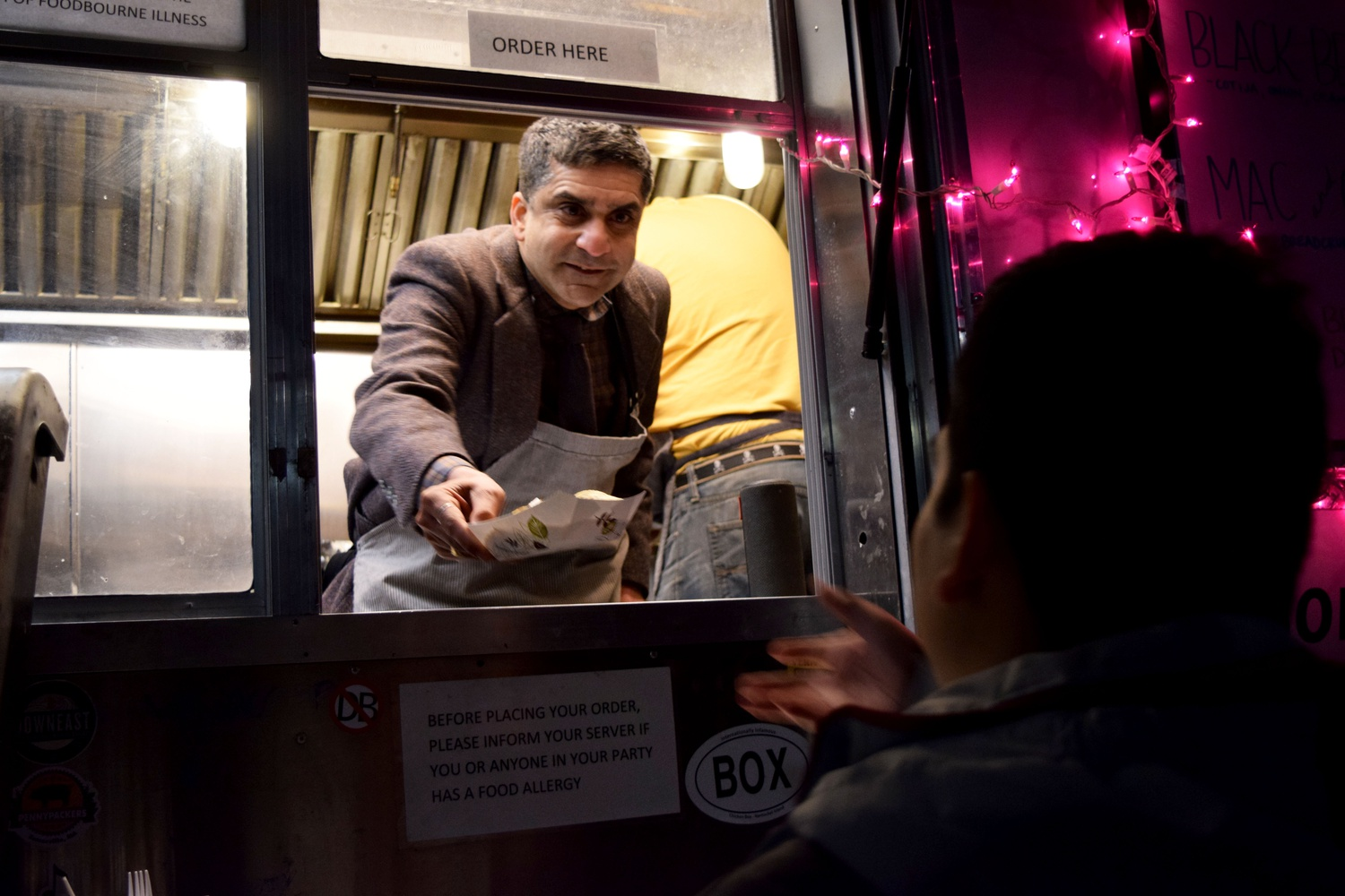 Dean of the College Rakesh Khurana hands out tacos to students Monday night outside Cabot House as a stress reliever during reading period.