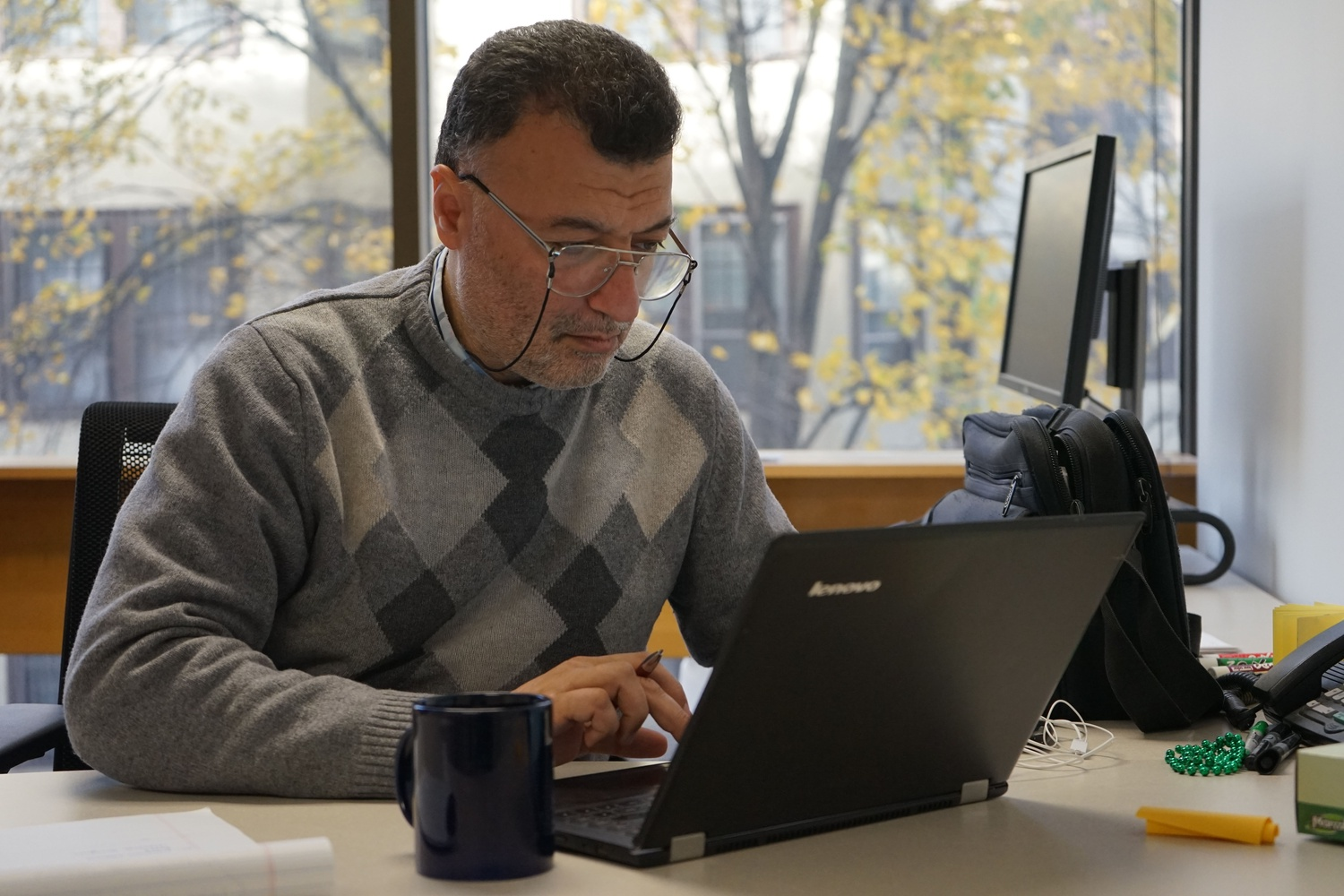 Mahmoud Hariri working at his desk in the Harvard Humanitarian Initiative office as a current Scholars at Risk fellow.