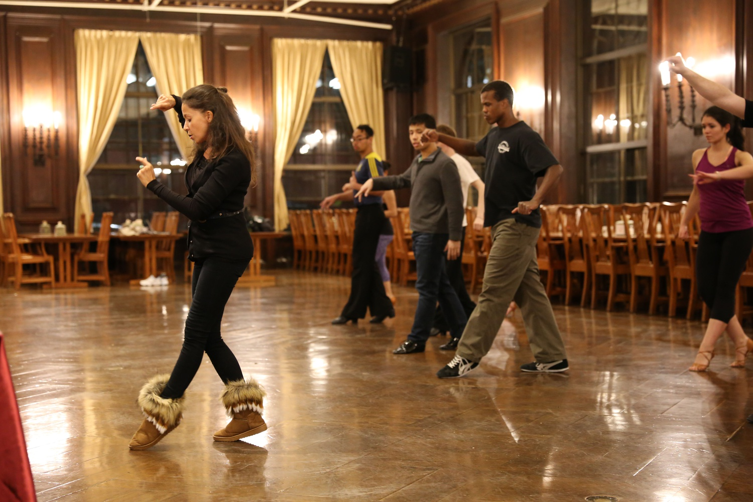 Olga Kinnard, a coach for the Harvard Ballroom Dance Team, teaches students during a free Wintersession dance lesson hosted by Harvard Ballroom in the Adams Dining Hall Wednesday night.