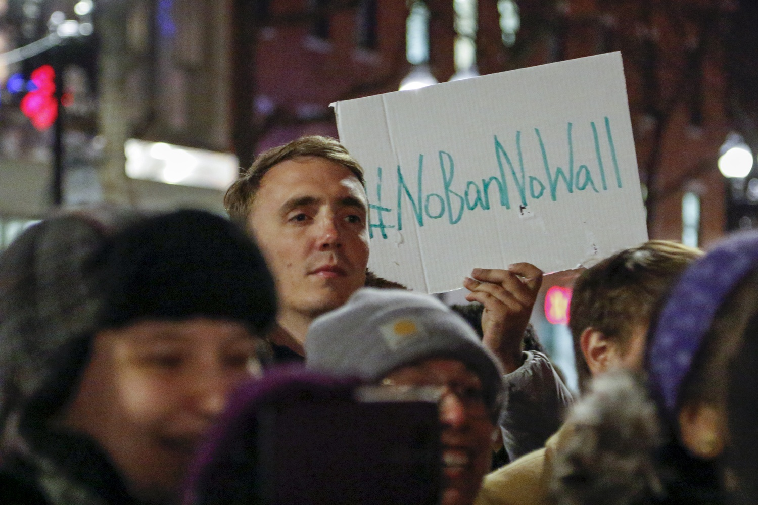 "A demonstrator holds a sign reading ""#NoBanNoWall"" during a rally in Harvard Square Friday night opposing recent immigration policy changes."