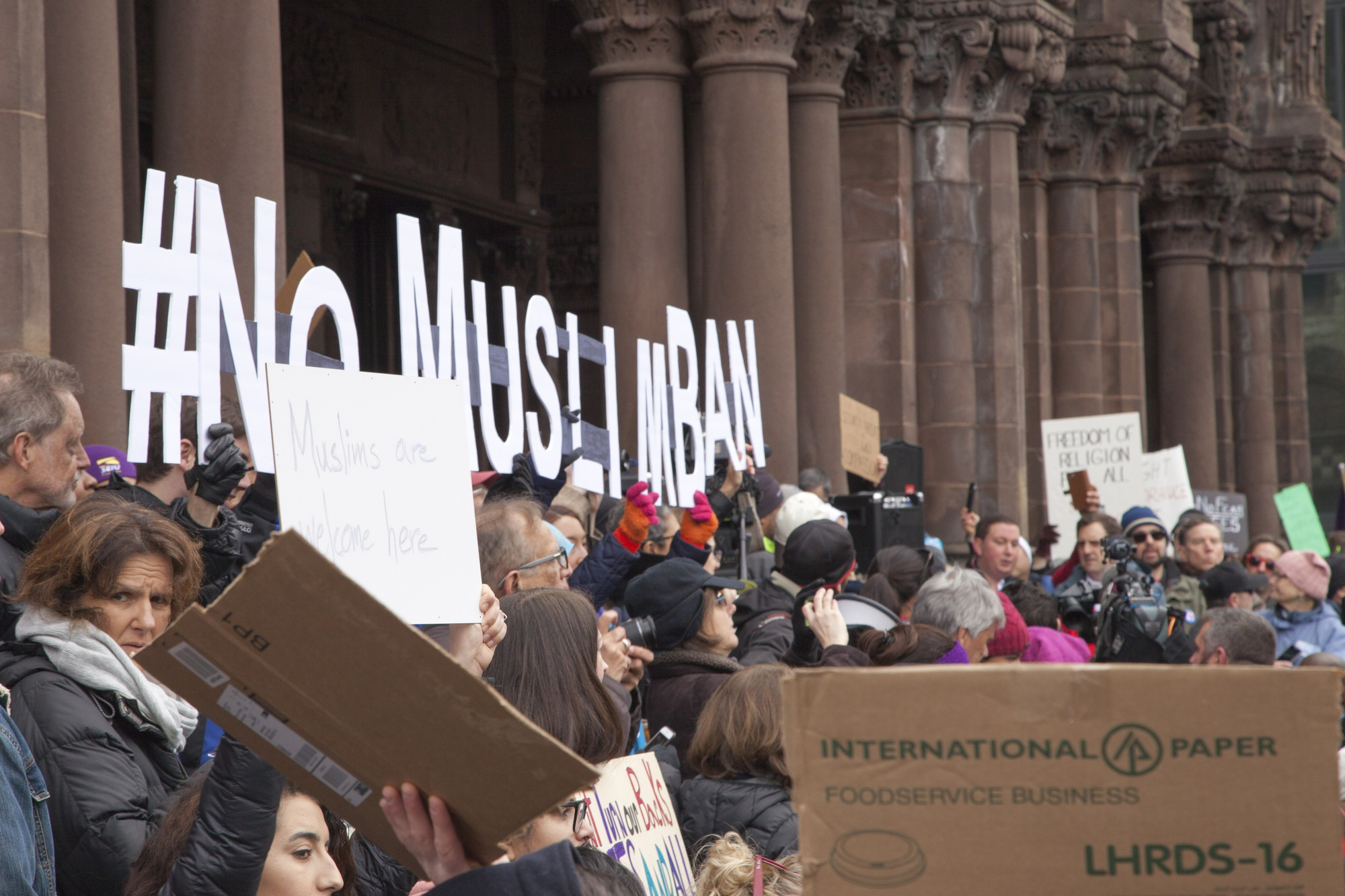 Demonstrators hold signs opposing President Donald Trump's immigration ban during a large rally in Boston's Copley Square Sunday afternoon.