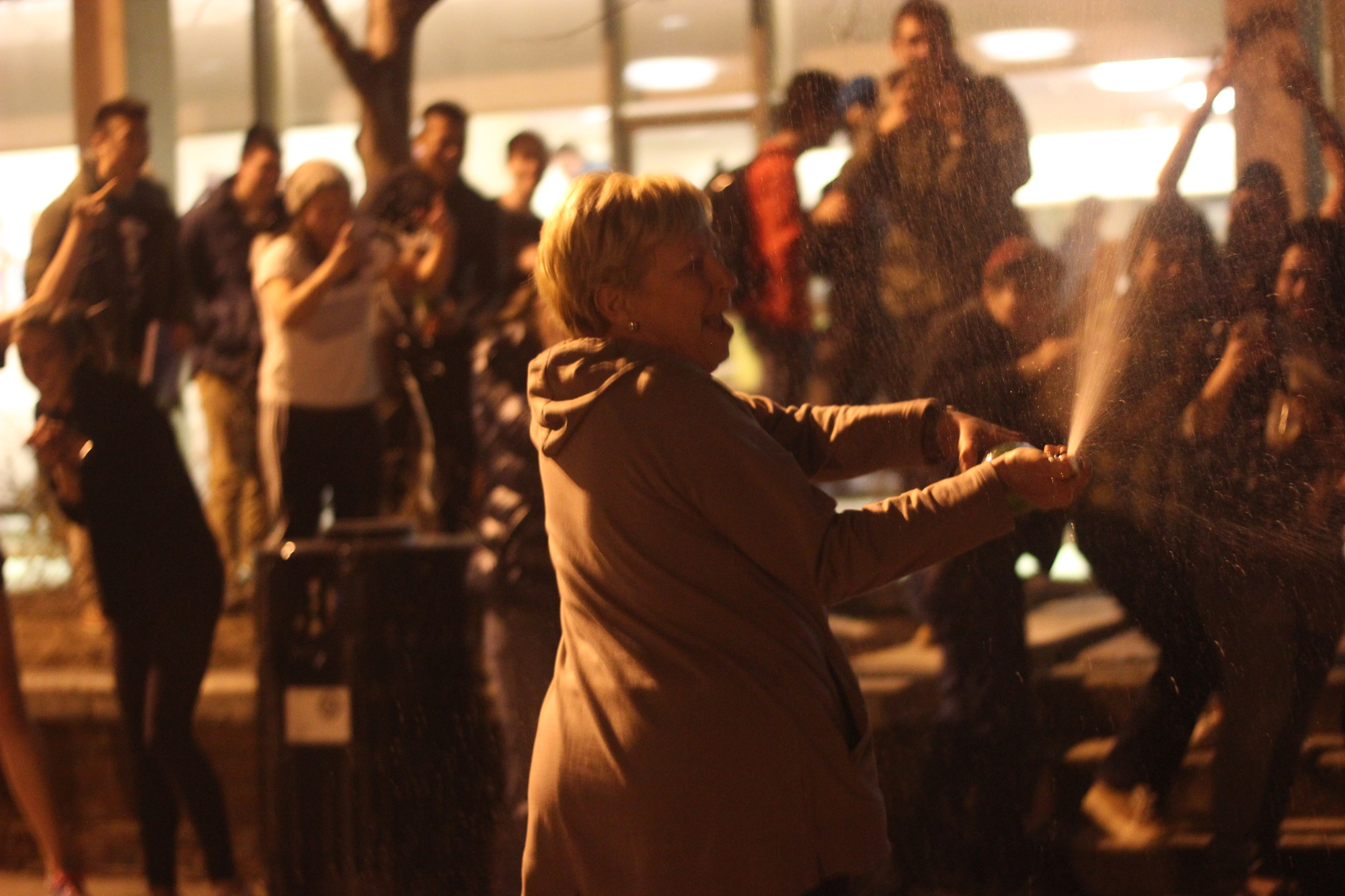 Quincy Faculty Dean Deborah J. Gehrke sprays champagne on students in the Quincy Courtyard on Sunday night in celebration of the New England Patriot's Super Bowl LI overtime upset.
