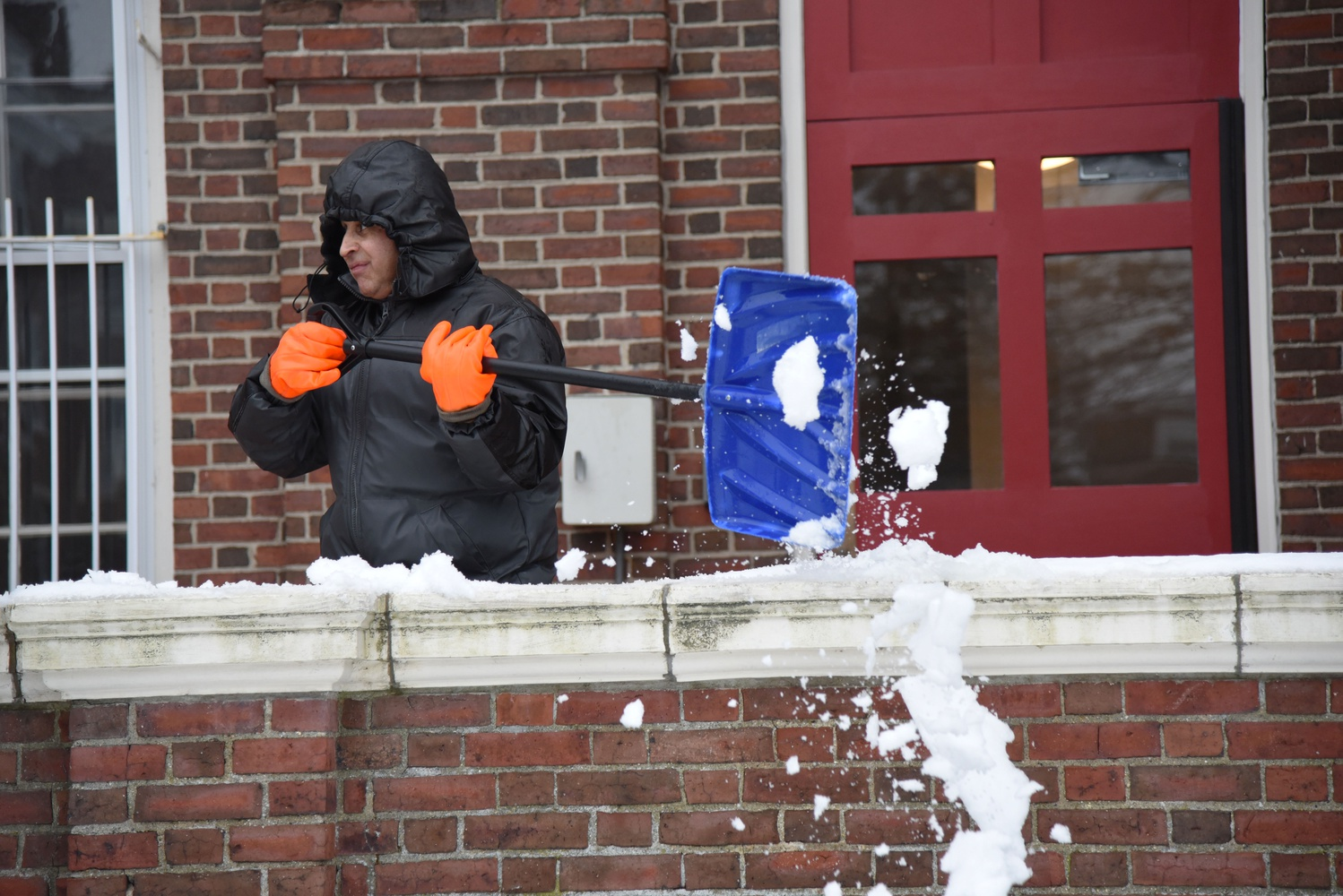 Jose O. Rodriguez shovels snow off a balcony of Cabot House Tuesday afternoon.