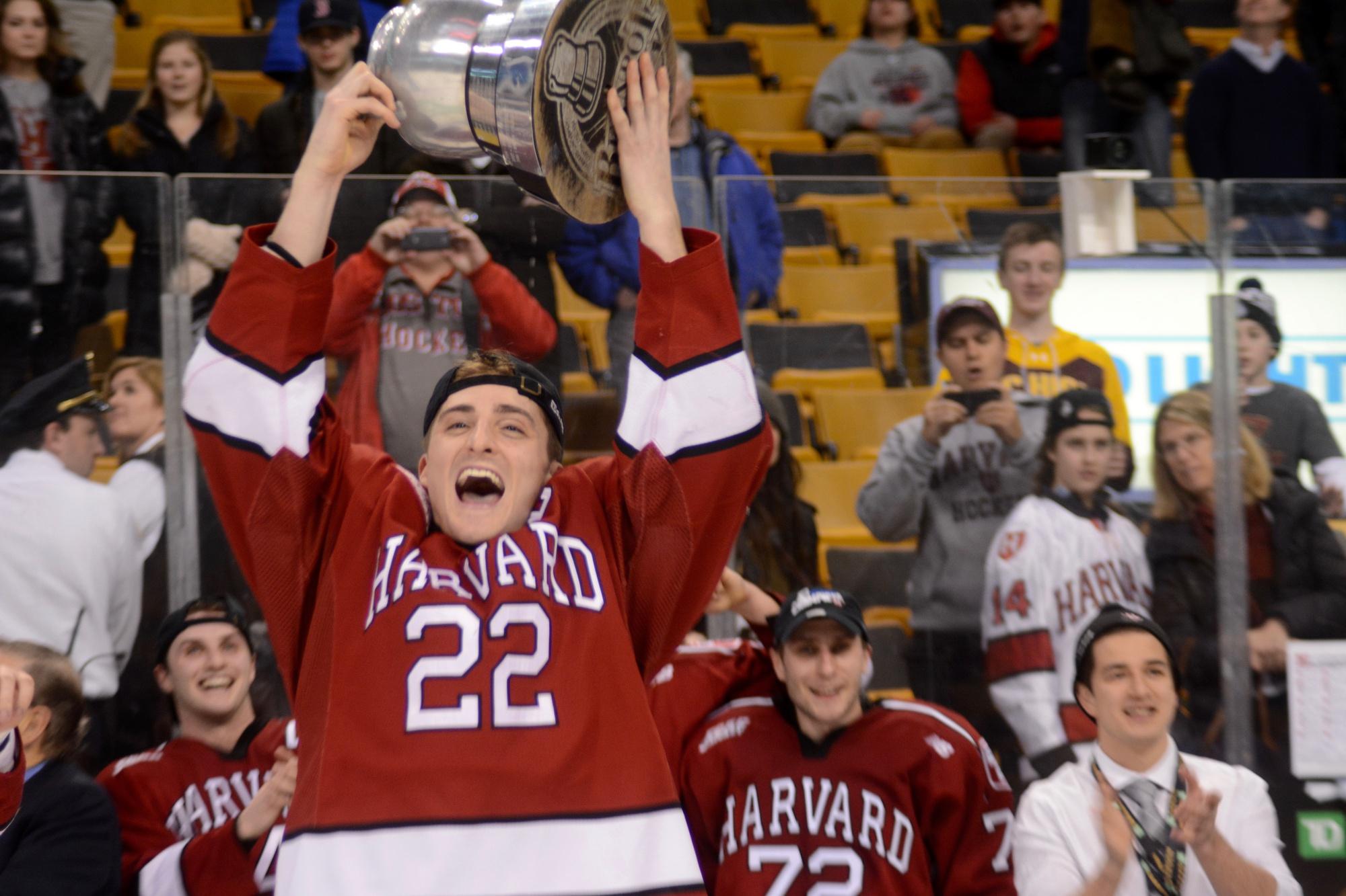 Co-captain Devin Tringale hoists Harvard's first Beanpot trophy since 1993.