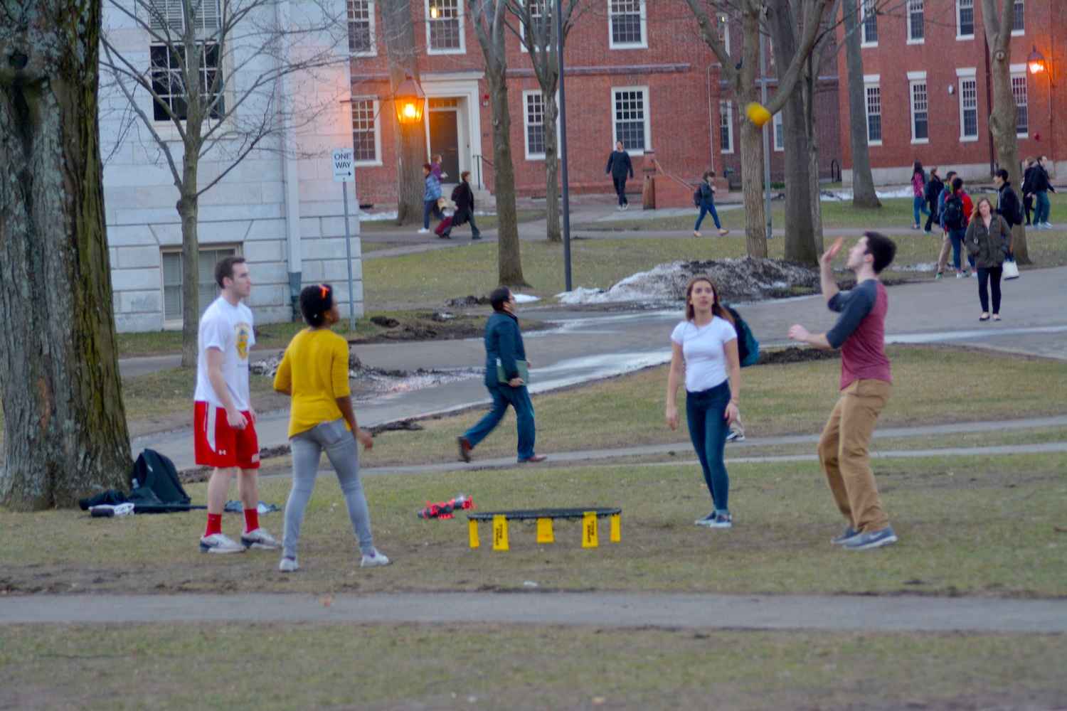 Students enjoy the unusually warm weather with a game of Spikeball in Harvard Yard Thursday afternoon.