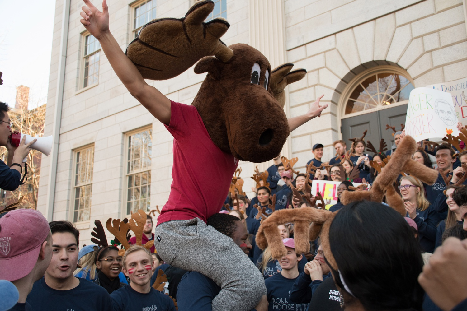 Victor C. Agbafe '19 carries a fellow Dunster resident, dressed as the House mascot - the moose - on his shoulders outside University Hall ahead of delivering housing assignments to freshmen.