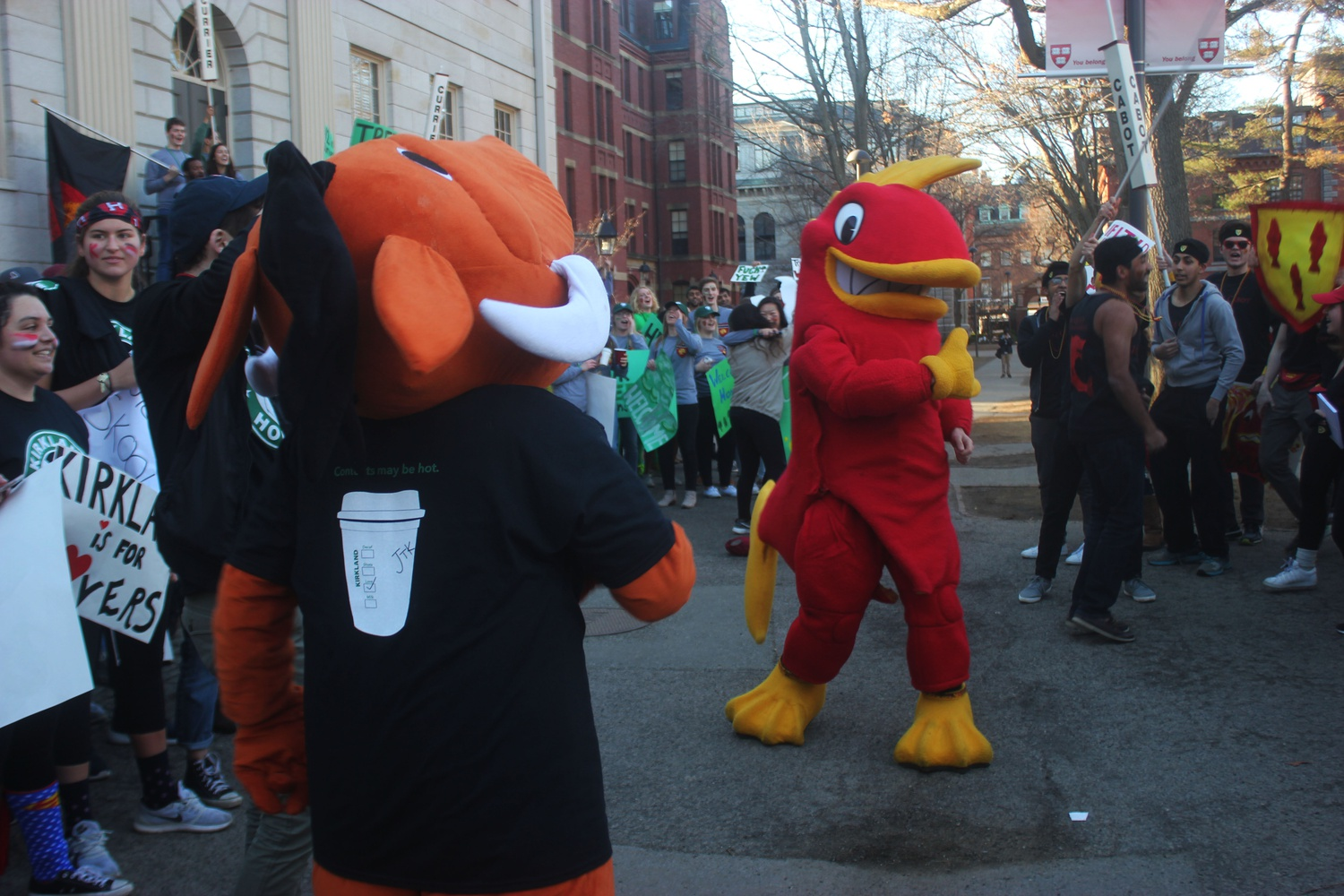 The Cabot and Kirkland mascots prepare for a dance battle in front of the John Harvard statue.