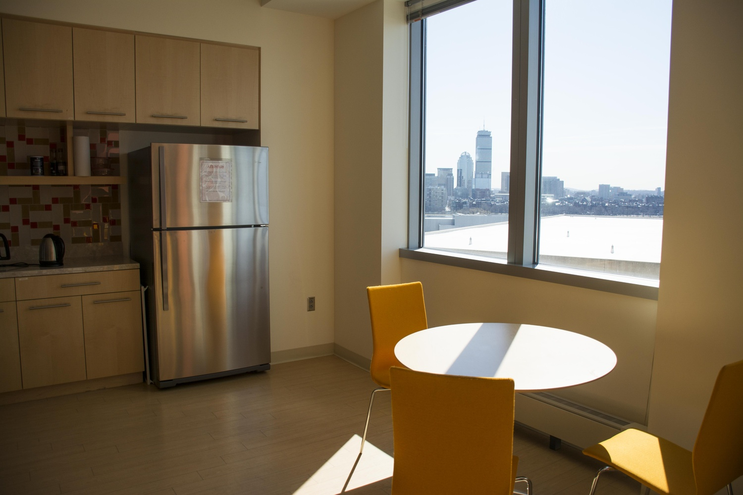 The kitchen where Zhang and his team eat their takeout meals has broad views of the Boston skyline.