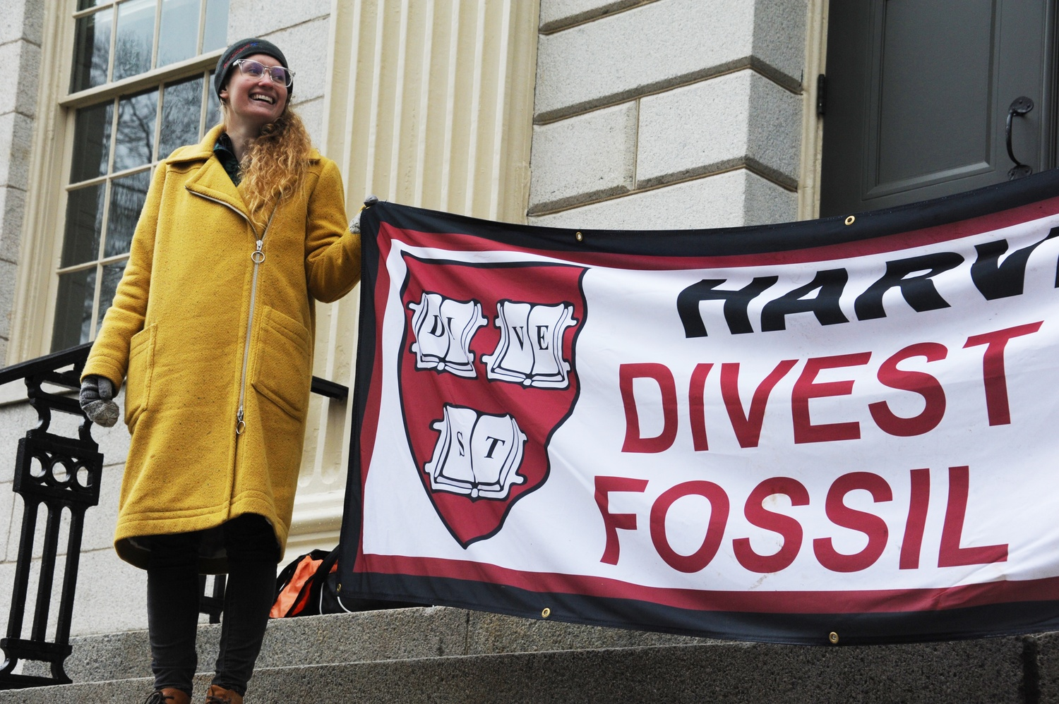 Kirsi Anselmi-Stith '18 holds up a Divest Harvard banner in front of University Hall. Around 20 members of the group blockaded entrances to the building Wednesday morning in protest of Harvard's decision not to divest from the coal industry.