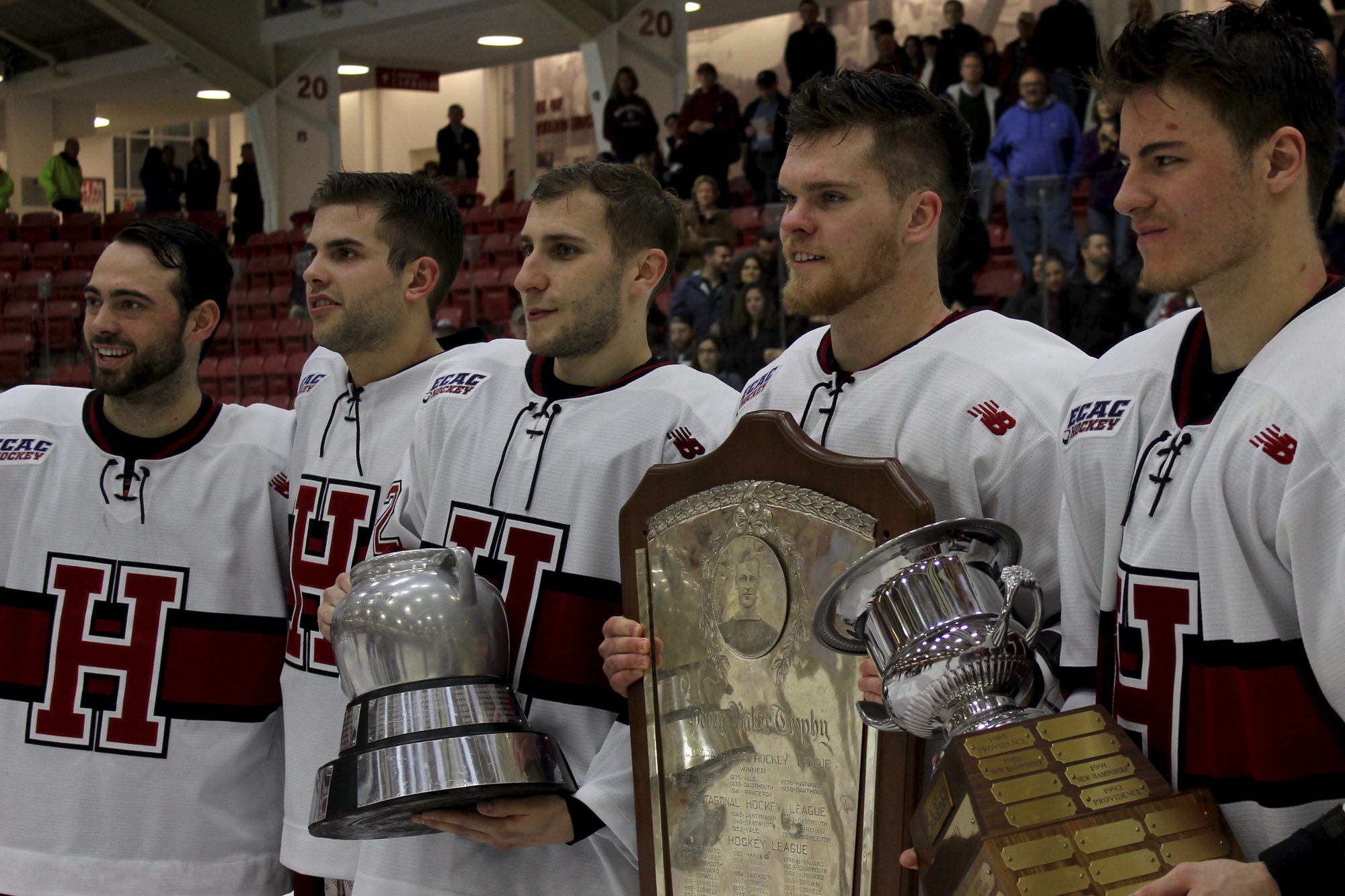 Phil Zielonka holds the Beanpot trophy, Sean Malone holds the Ivy League championship trophy, and Tyler Moy holds a stand-in for the ECAC regular-season championship trophy.