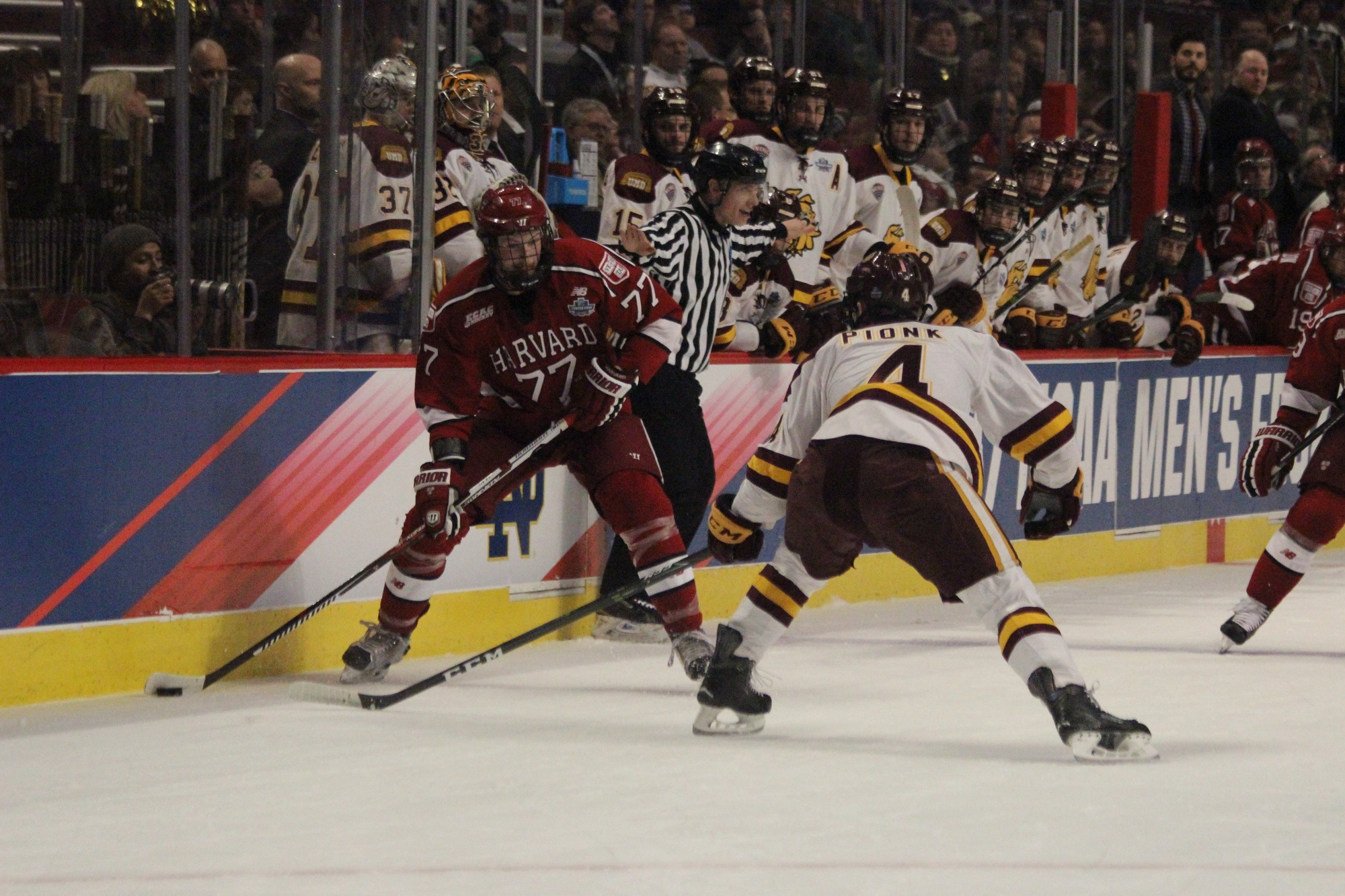 Sophomore Lewis Zerter-Gossage carries the puck during the first period of Harvard's Frozen Four bout with Minnesota-Duluth.