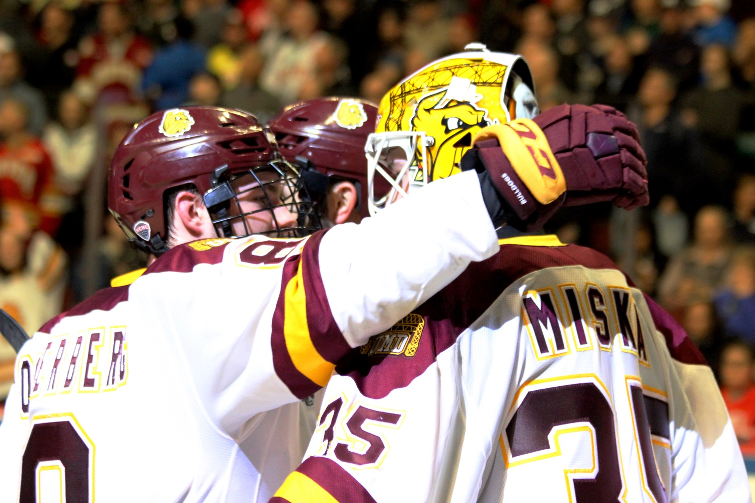 Minnesota-Duluth forward Kyle Osterberg hugs goaltender Hunter Miska in celebration of their win over the Crimson. Minnesota-Duluth advances to the NCAA finals on Saturday.