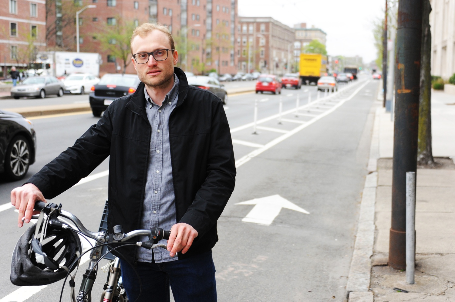Nathanael Fillmore, a Cambridge-based bicycle activist, stands in front of a protected bike lane he advocated for on Massachusetts Ave.