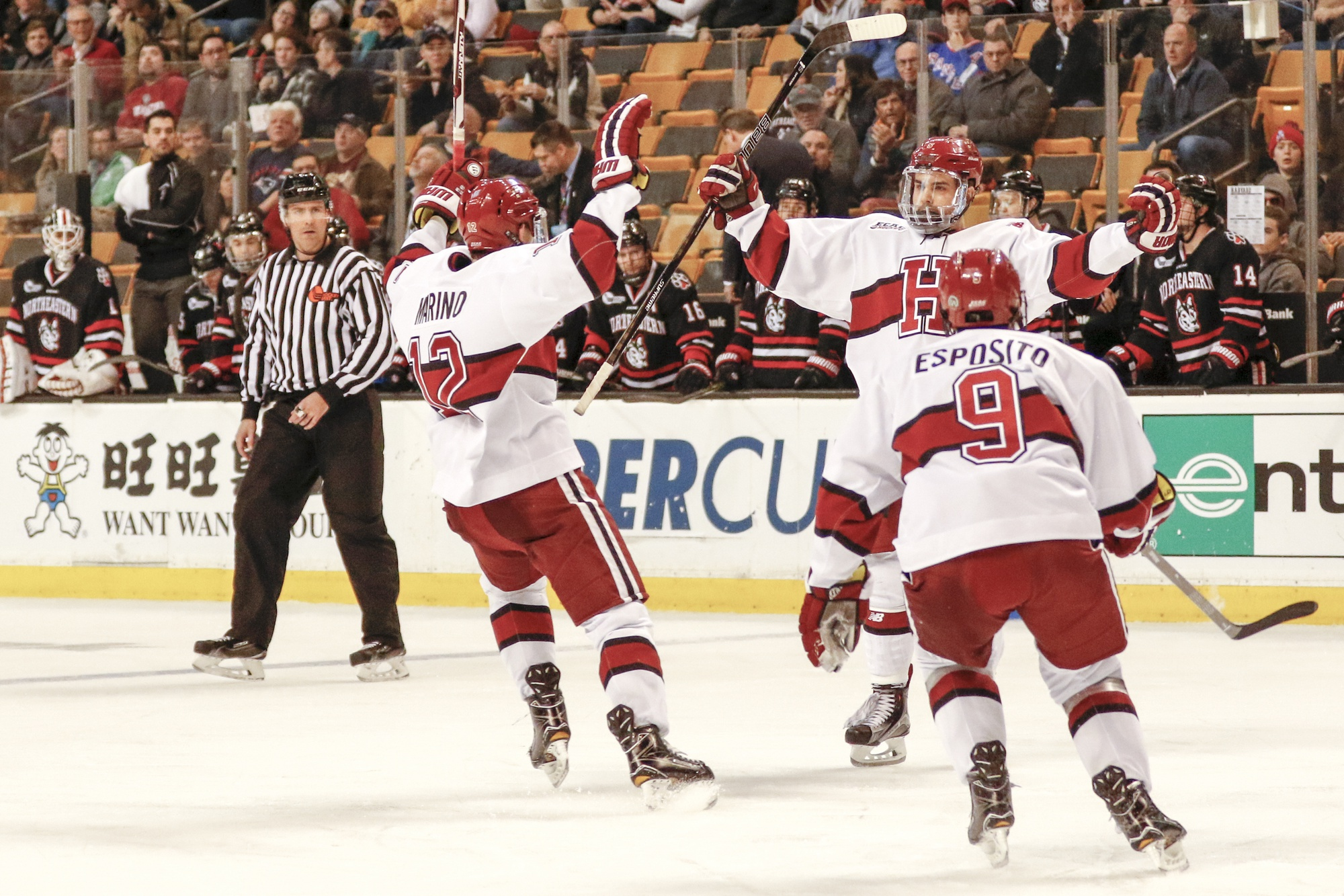 Crimson players exult after a goal in the first round of the Beanpot against Northeastern.