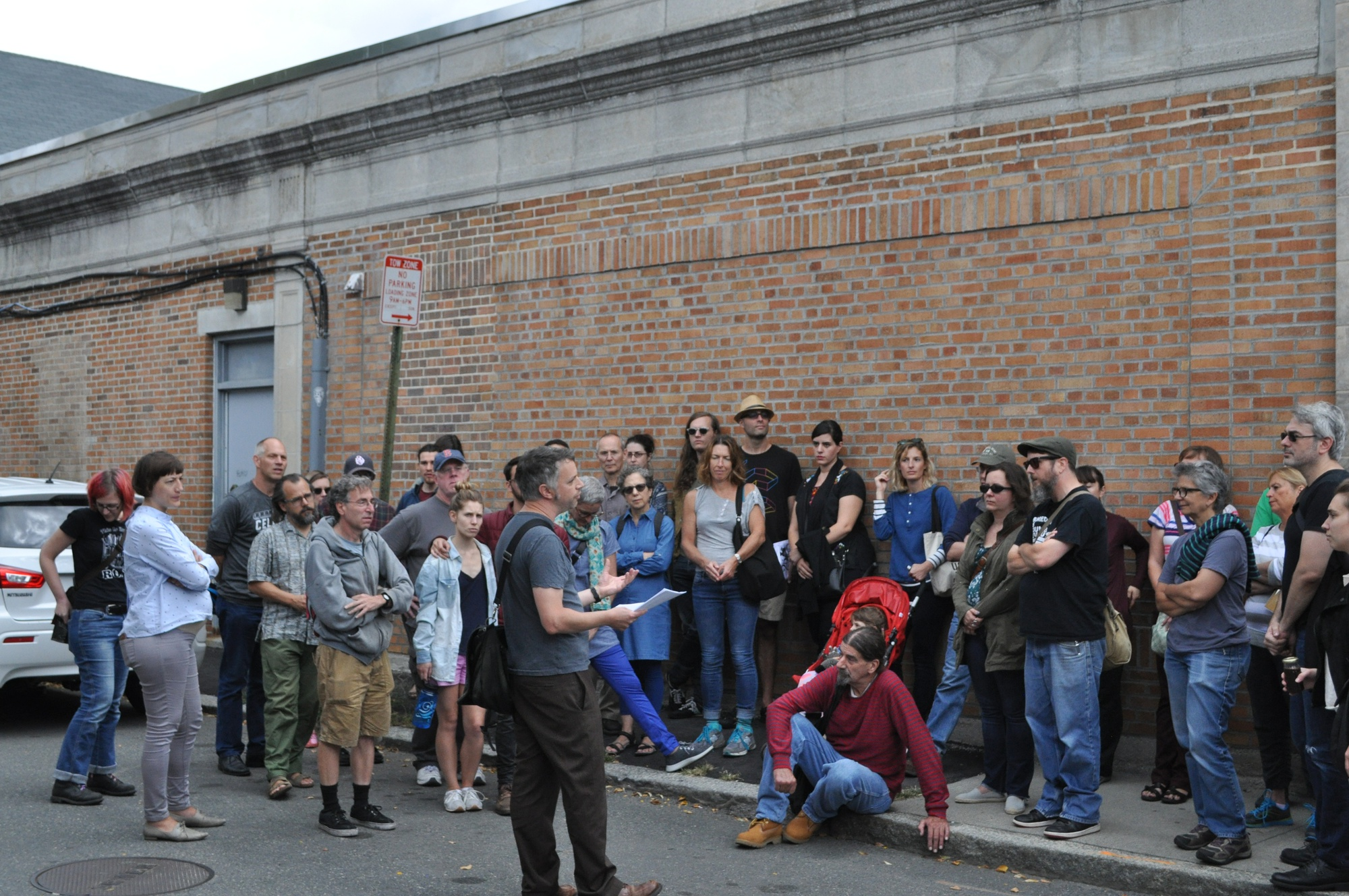 Tim Devin speaks to a crowd of over 60 people who have gathered for the counterculture walking tour of Inman Square.