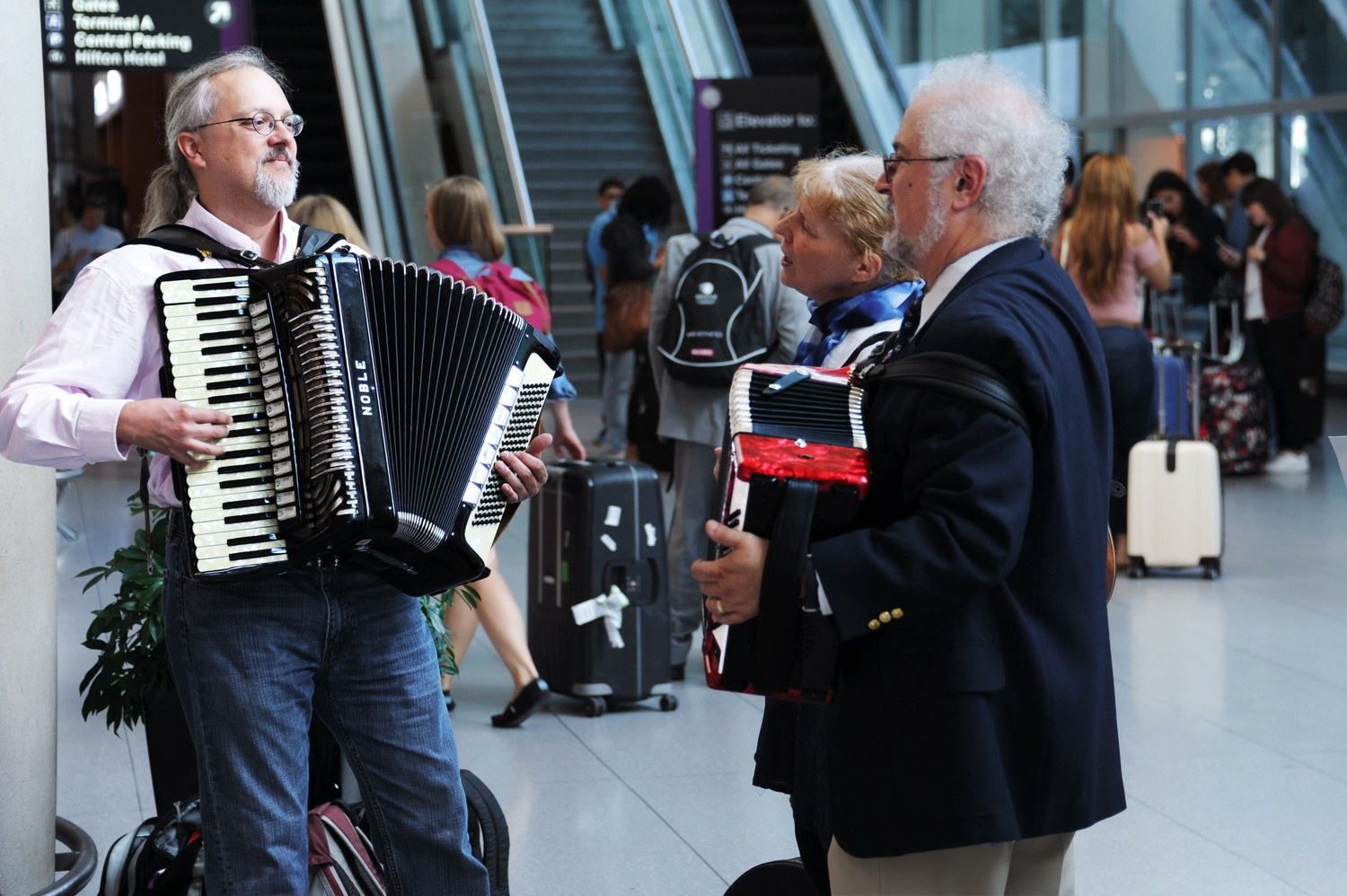 Professor Thomas M. Michel '77, right, plays the accordion as he and others await the arrival of Iranian scientist Seyed S. S. Saravi at Logan International Airport Wednesday afternoon.