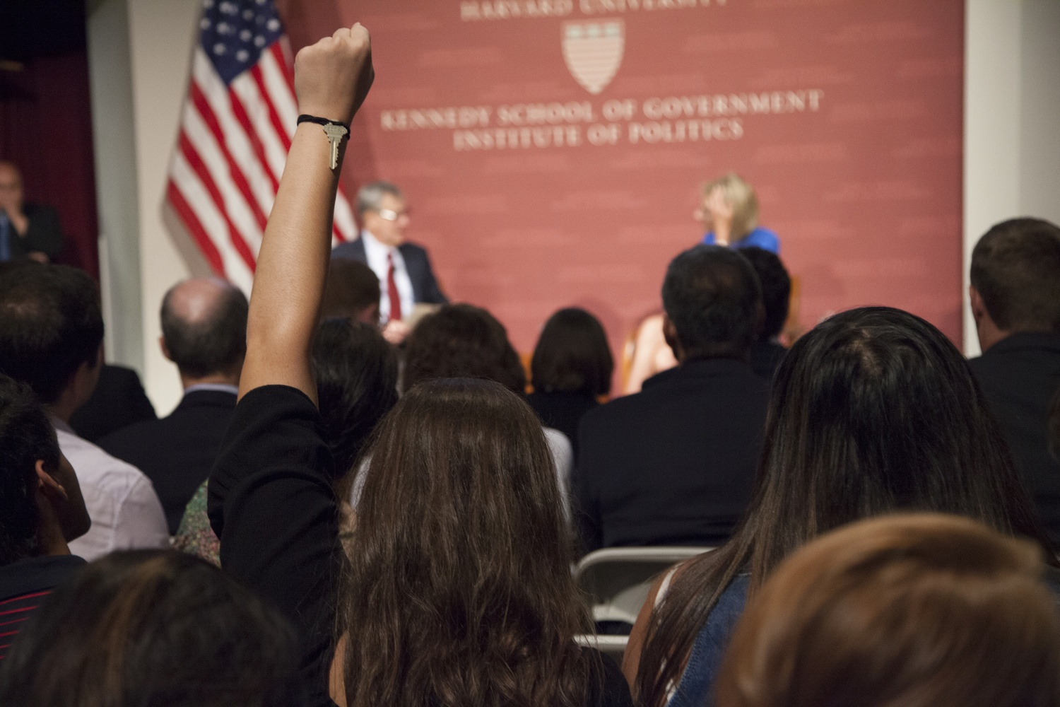 A student raises her fist in the air in an act of silent protest against Secretary of Education Betsy DeVos Thursday evening. Hundreds of students and locals turned out to protest DeVos' speech at the Harvard Kennedy School.