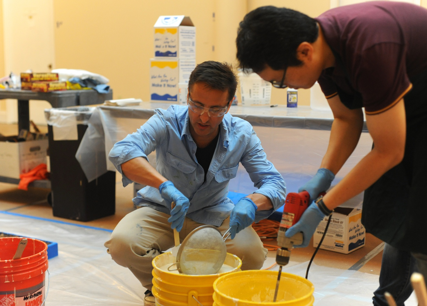 "Adam J. Aja, the assistant curator of collections at the Harvard Semitic Museum, demonstrates proper sieving technique for the production of plaster casts. Aja and his team worked to cast the ""Dream Stele"" of King Thutmose IV."