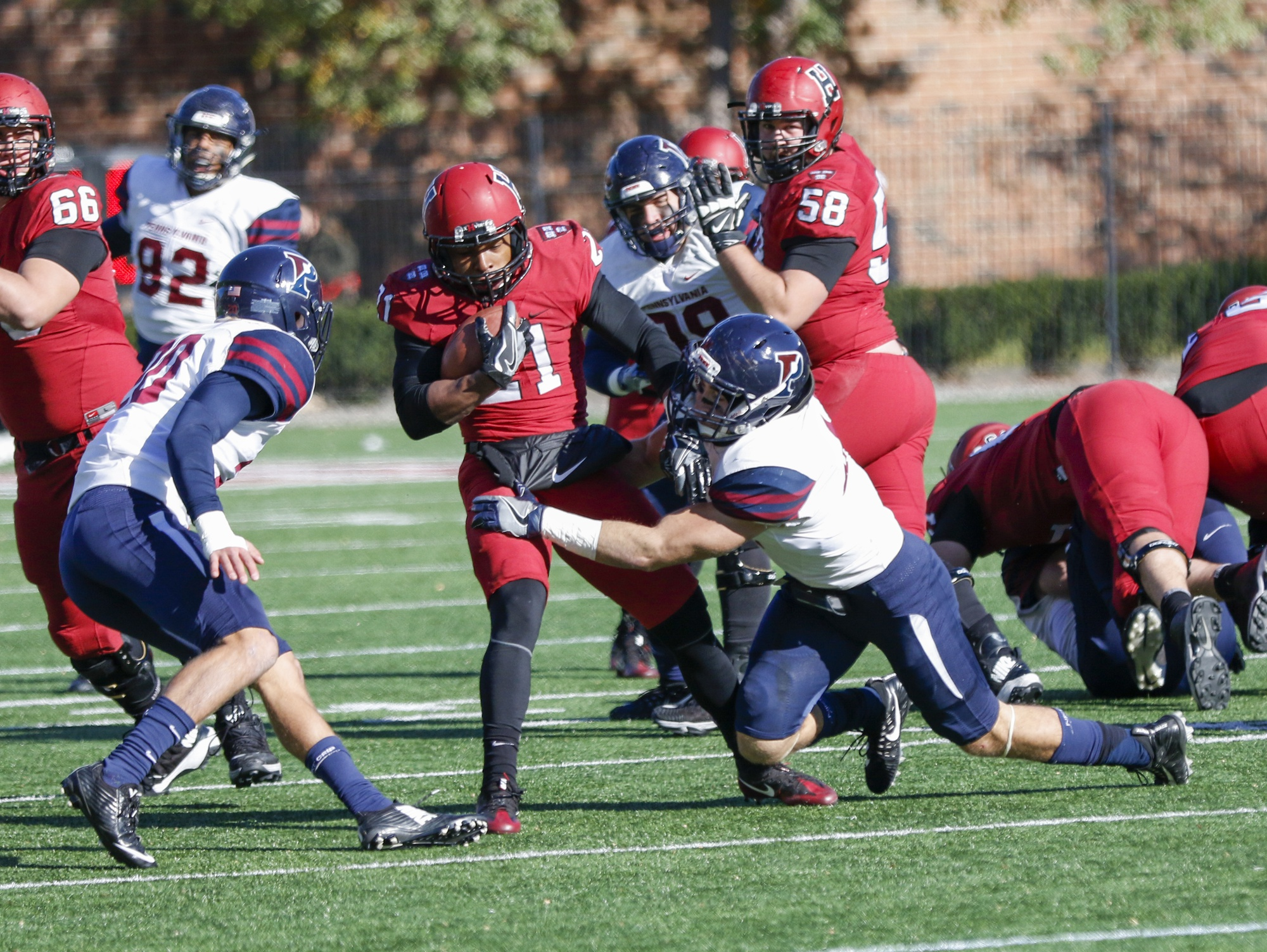 Quakers tacklers wrap up junior running back Charlie Booker. The rusher finished with 35 yards, his lowest total of the year, and two fumbles.