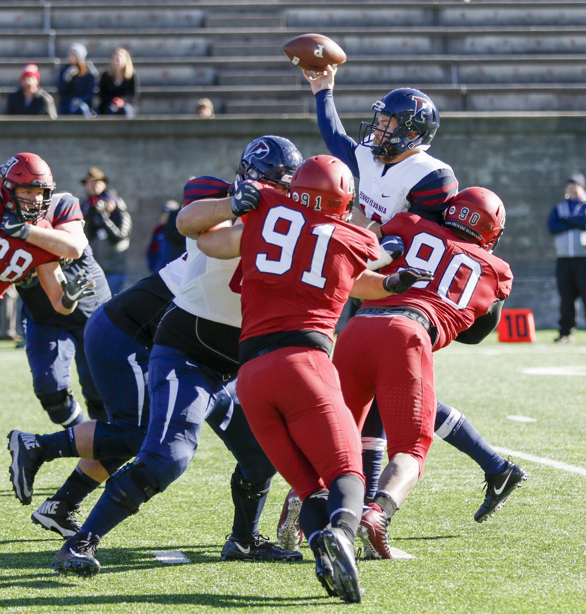 Harvard senor defensive tackle Stone Hart delivers a blow on Penn senior quarterback Will Fischer-Colbrie. The Penn signal-caller completed 13 of 25 passes for 130 yards and a score against the Crimson.
