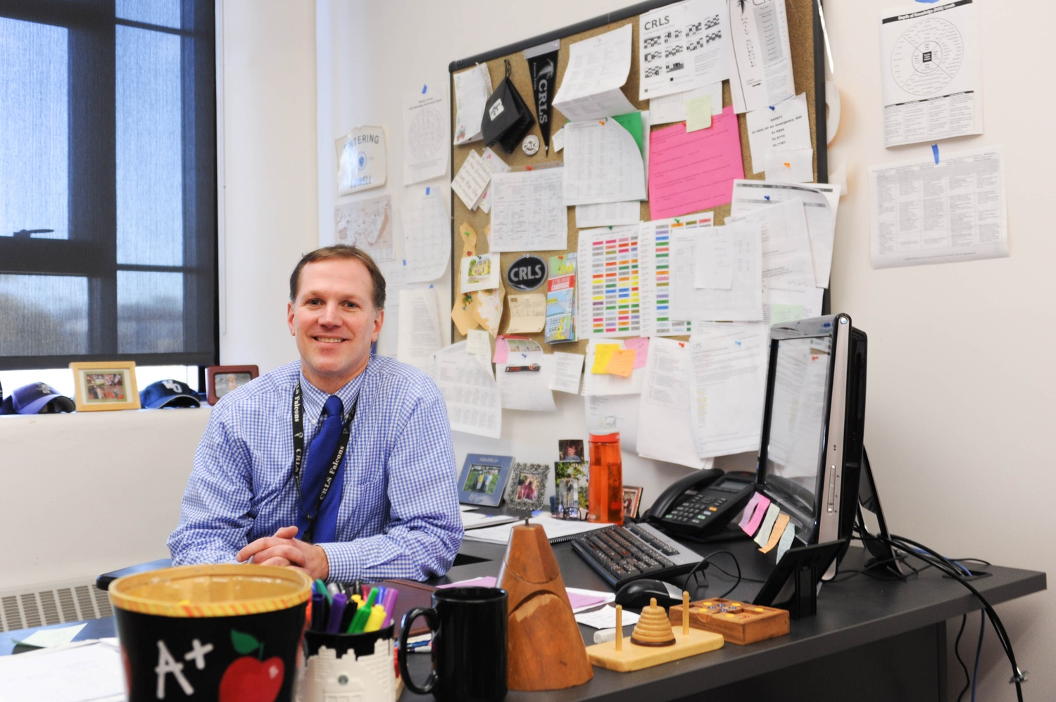 Jeff Gaglione, Dean of Mathematics at Cambridge Rindge and Latin School, poses for a photo at his desk Thursday afternoon.
