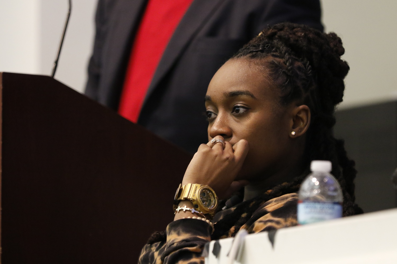Jackie Hill-Perry listens as Reverend Jonathan L. Walton speaks at religious group Harvard College Faith and Action's meeting Friday night. Some students criticized HCFA's decision to invite Hill-Perry, an outspoken critic of homosexuality.