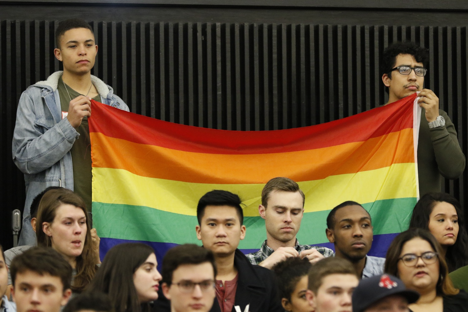 "Students hold up a rainbow flag in protest of Jackie Hill-Perry. Religious group Harvard College Faith and Action invited the ""ex-gay"" speaker to their weekly meeting Friday night."