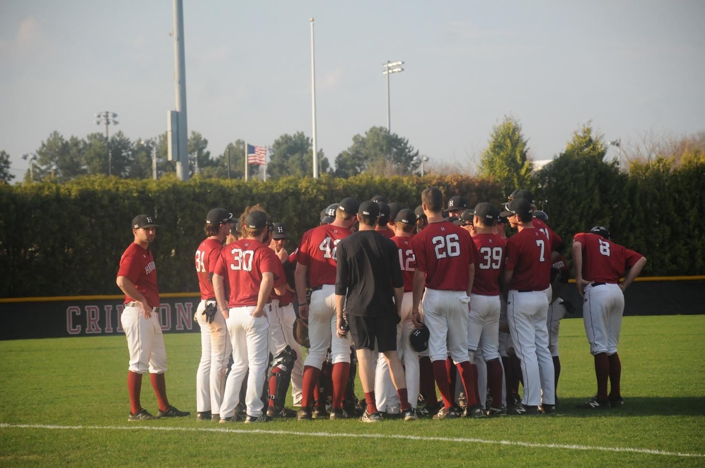 The baseball team huddles around Coach Decker.