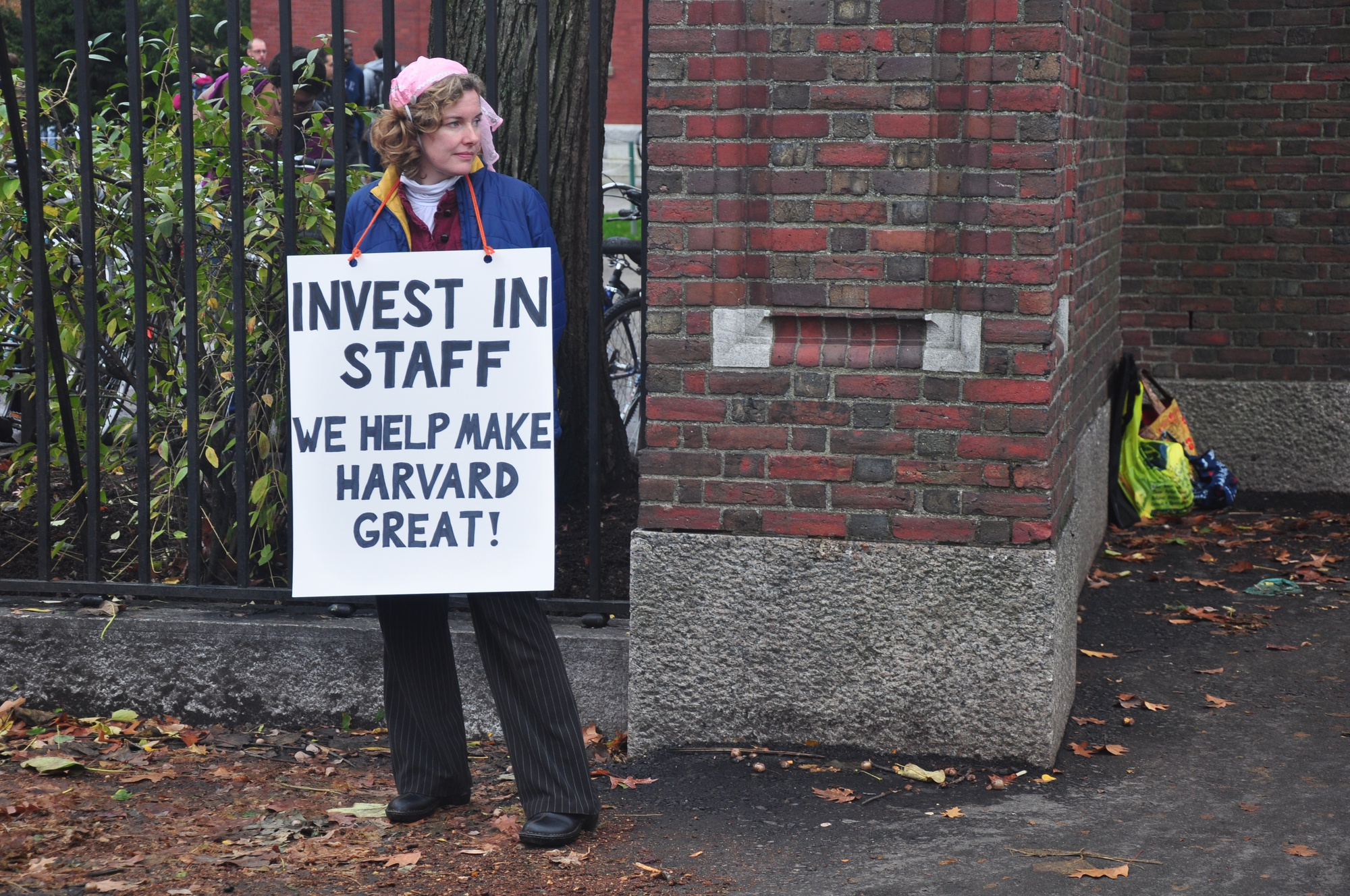 A member of the Harvard Union of Clerical and Technical Workers (HUCTW) wears a sign asking Harvard to invest in its staff in November of 2012.