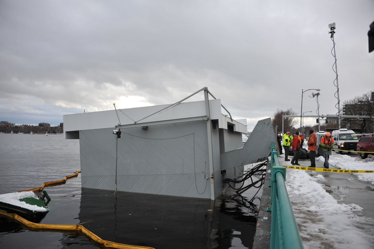 The Harvard Sailing Center sinks into the Charles River on Friday.