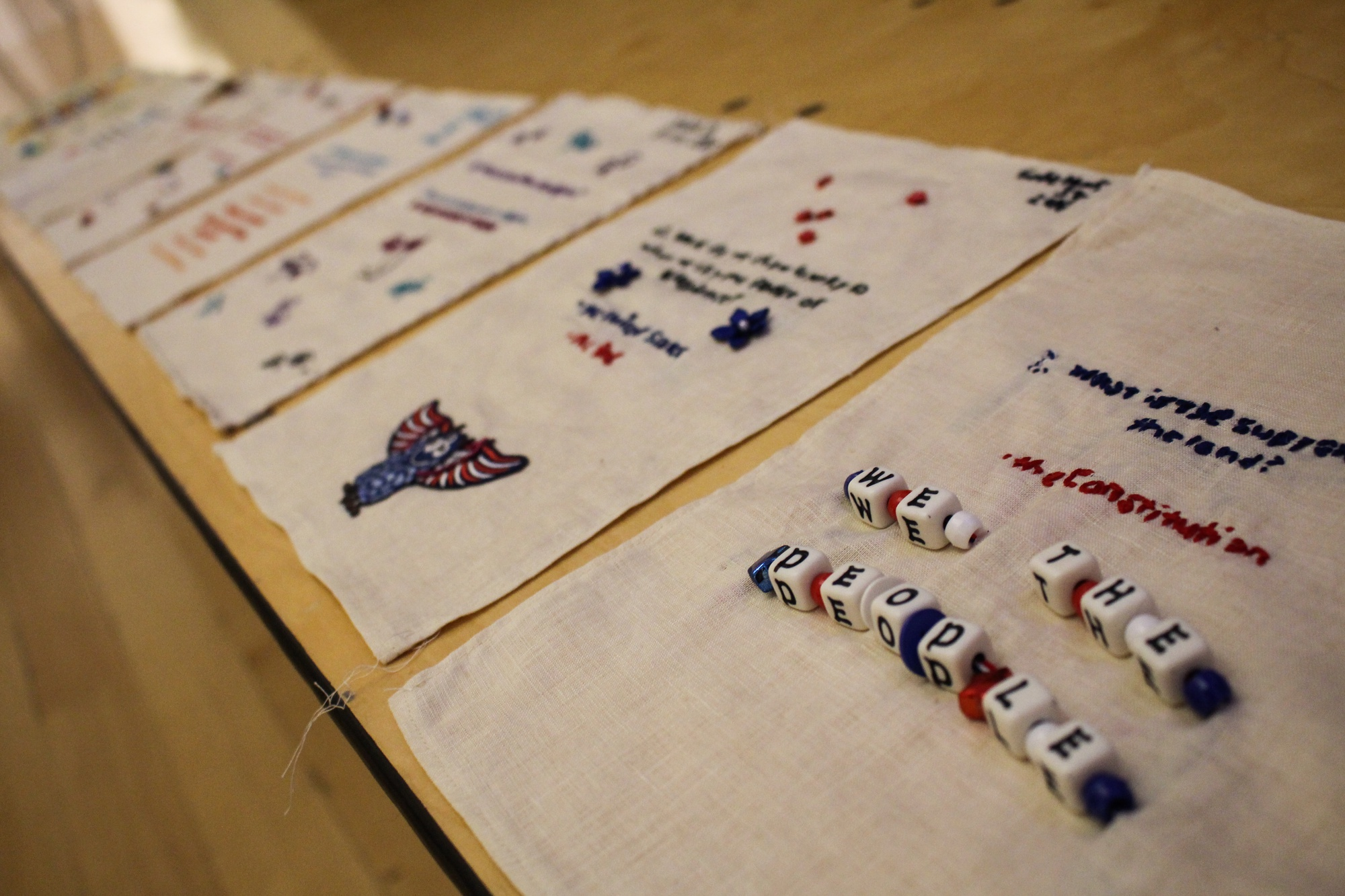 Workshop participants embroider samplers as they study for the naturalization test.