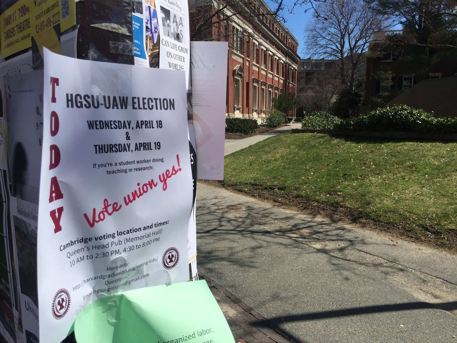 A pro-unionization poster hangs taped to a campus postering board on the first day of voting in Harvard's second unionization election.
