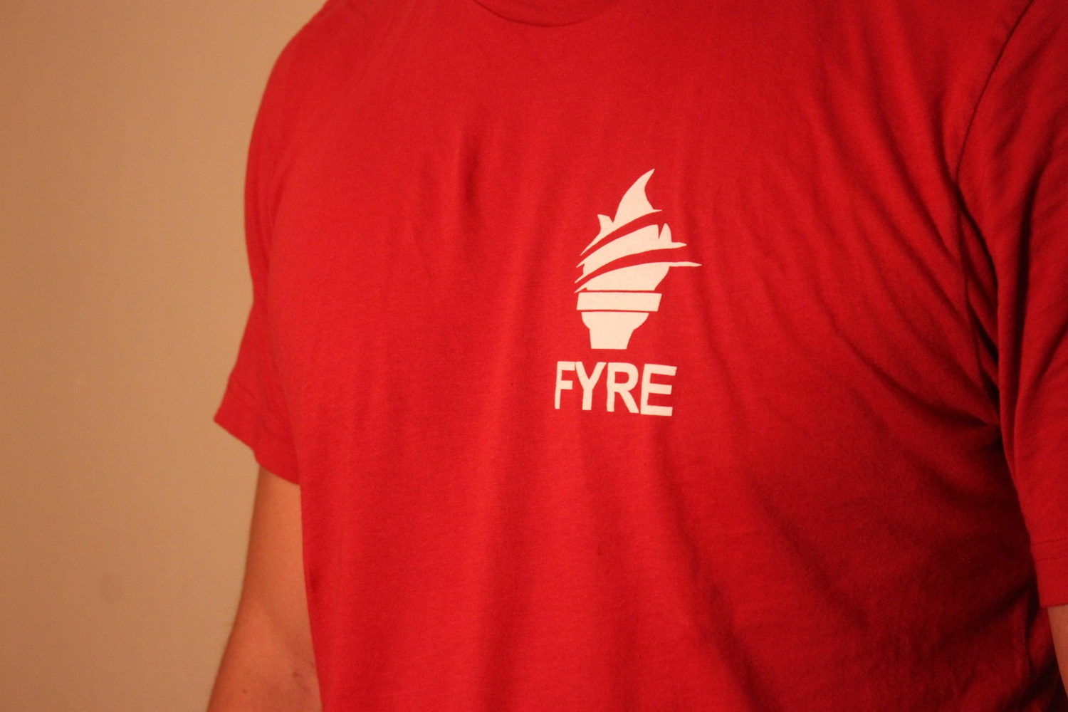 A student poses wearing a FYRE t-shirt.