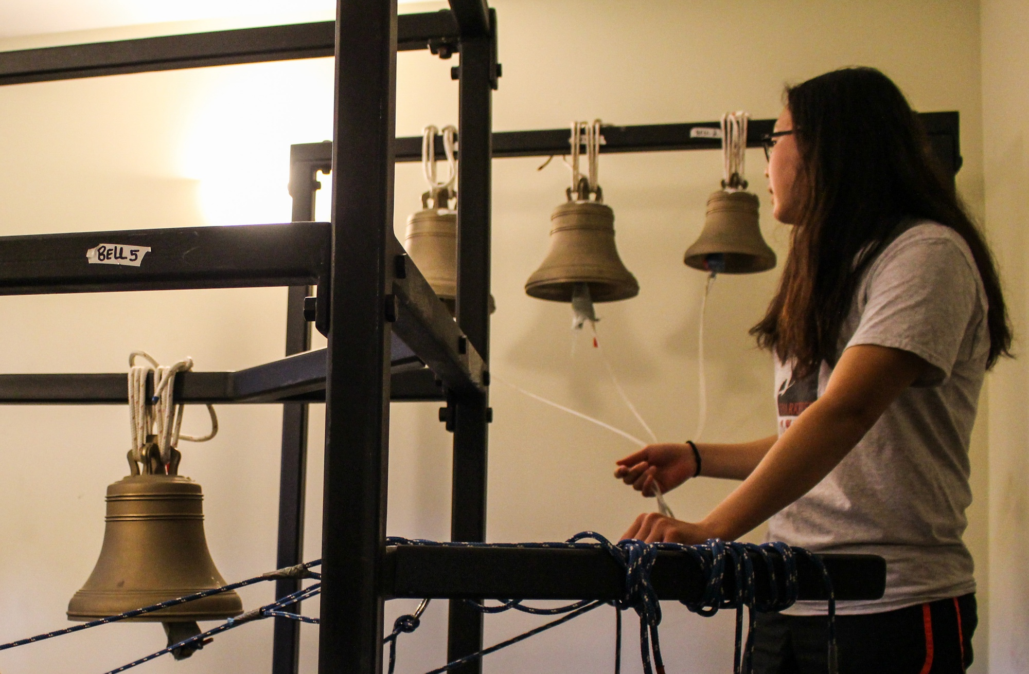 Jessica Ding '19, a member of the Lowell House Society of Russian Bell Ringers, rings the bells in the basement of 20 Prescott Street.