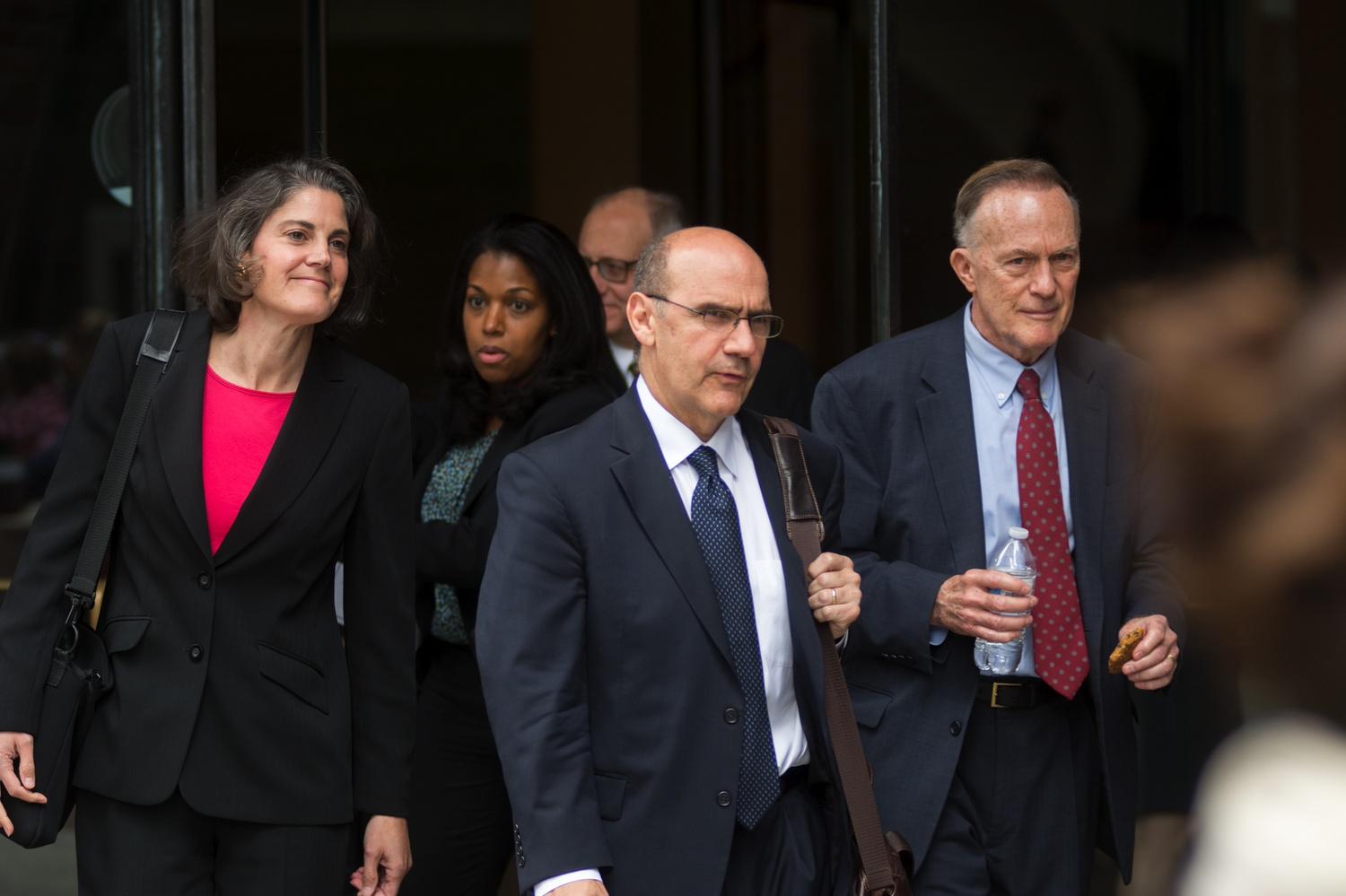 Harvard's long-serving Dean of Admissions and Financial Aid William R. Fitzsimmons '67 (far right) exits the courthouse during the admissions trial.