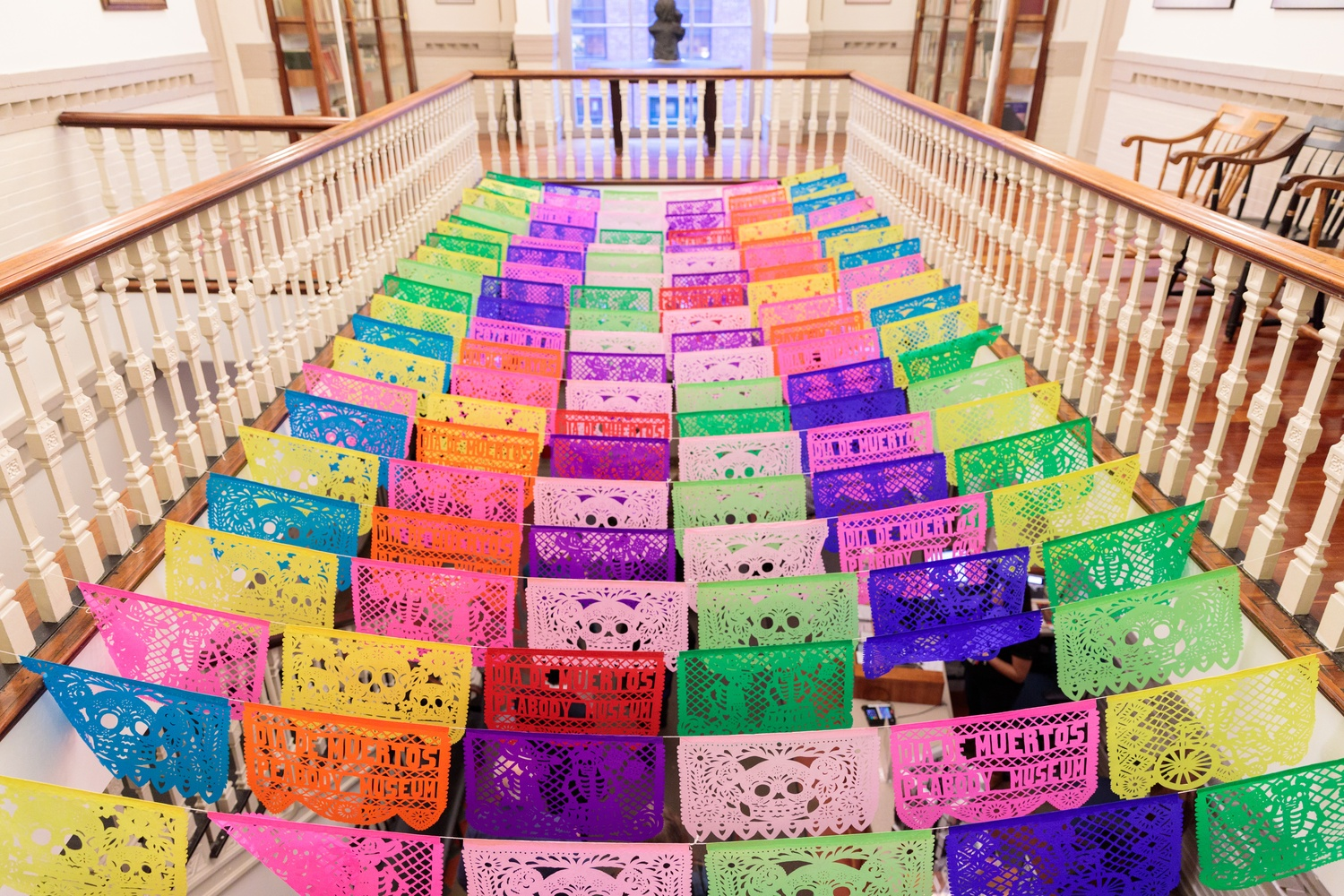 Papel picado (perforated paper) hangs between the stair railings at the Peabody Museum during its Day of the Dead party Thursday.