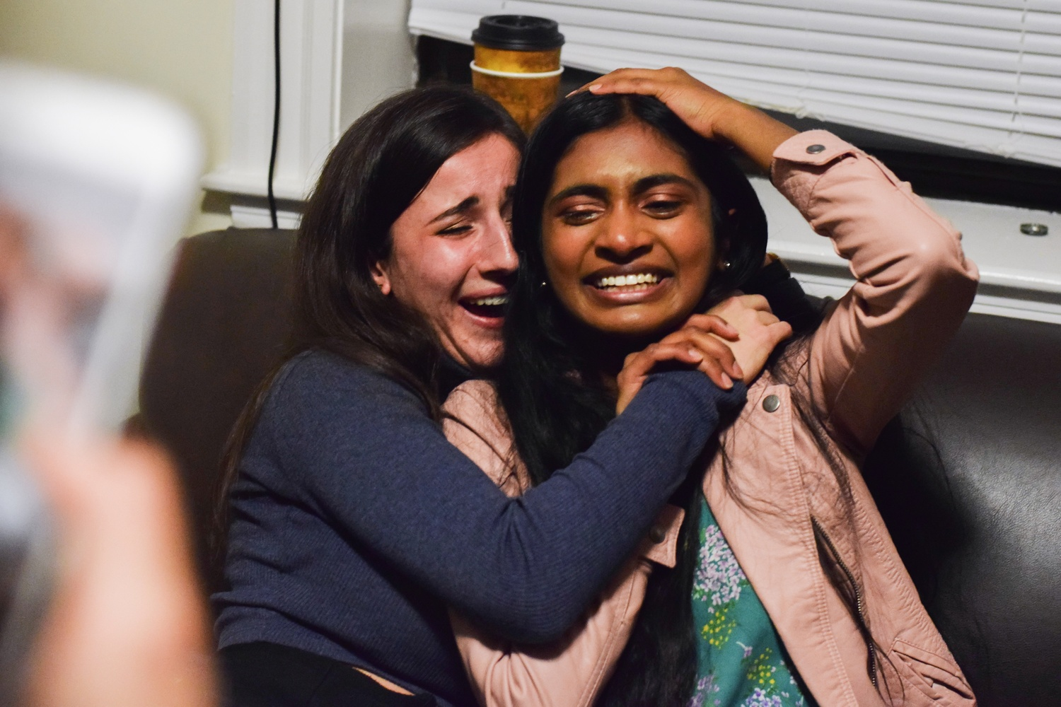 Sruthi Palaniappan '20 (right) and Julia M. Huesa '20 (left) collapse onto a couch after hearing that they won the Undergraduate Council presidential election.
