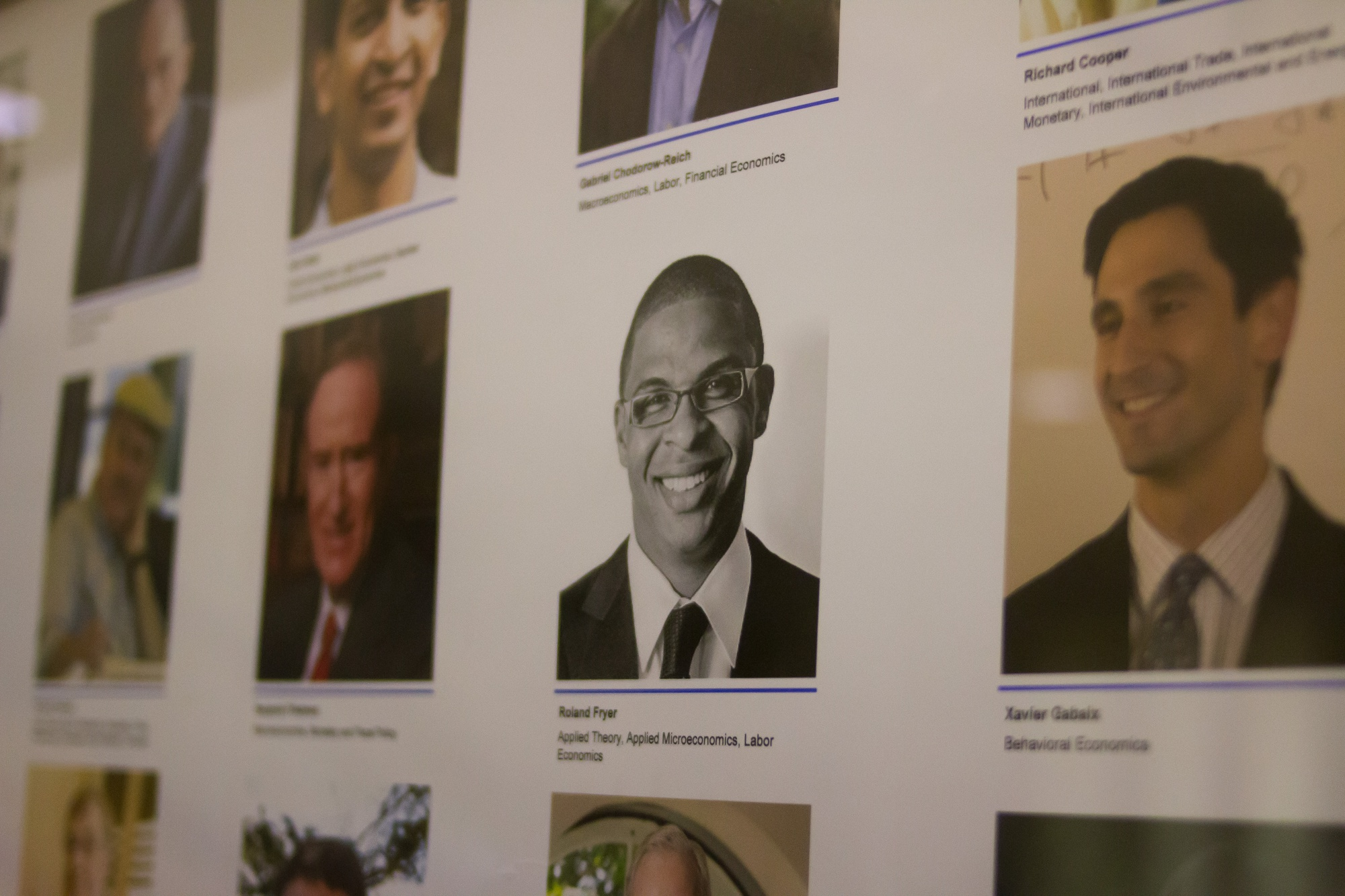 A headshot of Economics professor Roland G. Fryer, Jr. among other department faculty in the Littauer Center.
