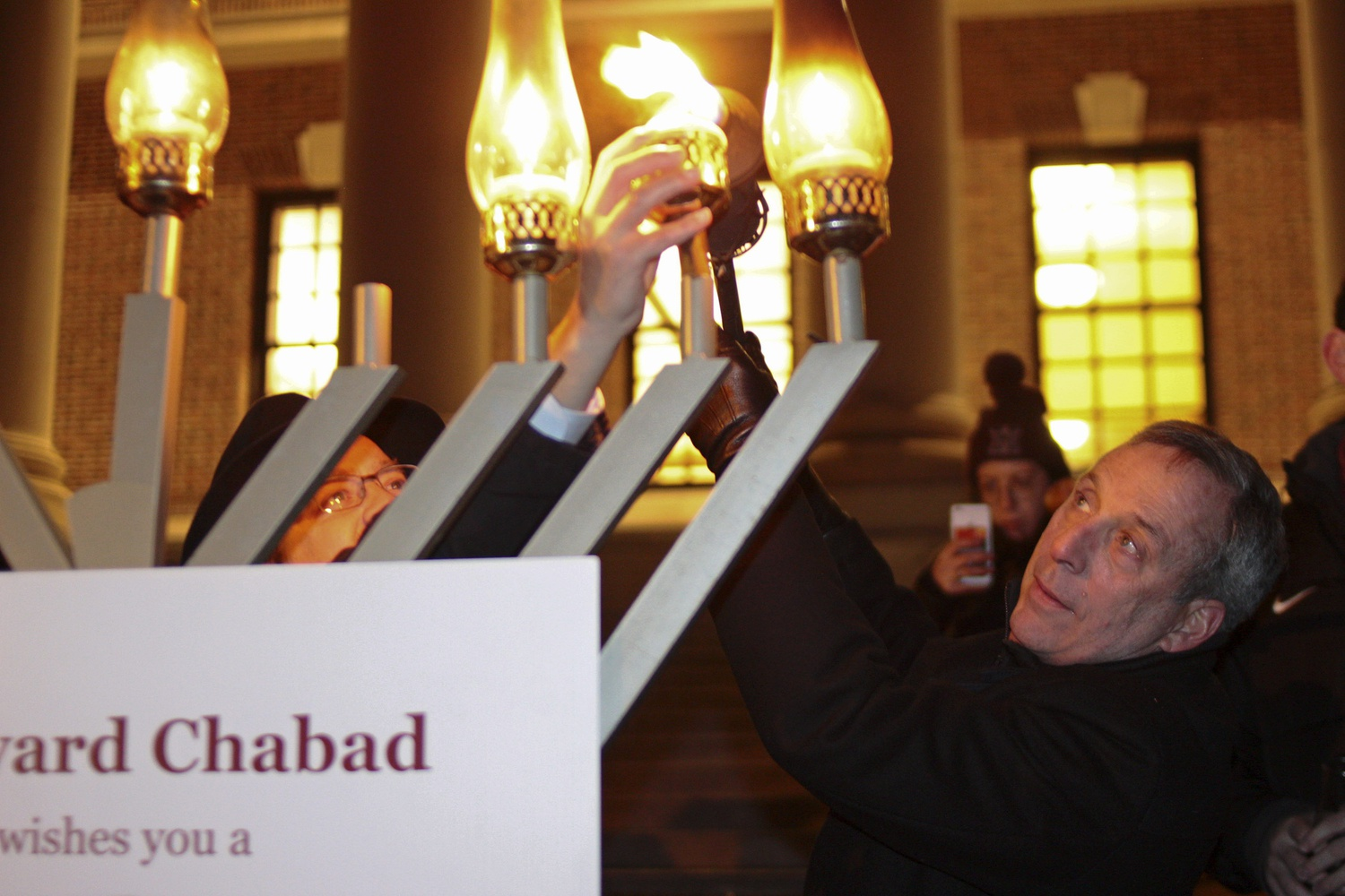 President Bacow helps light a large menorah in front of Widener Library during Harvard Chabad's annual Grand Menorah Lighting Tuesday evening.