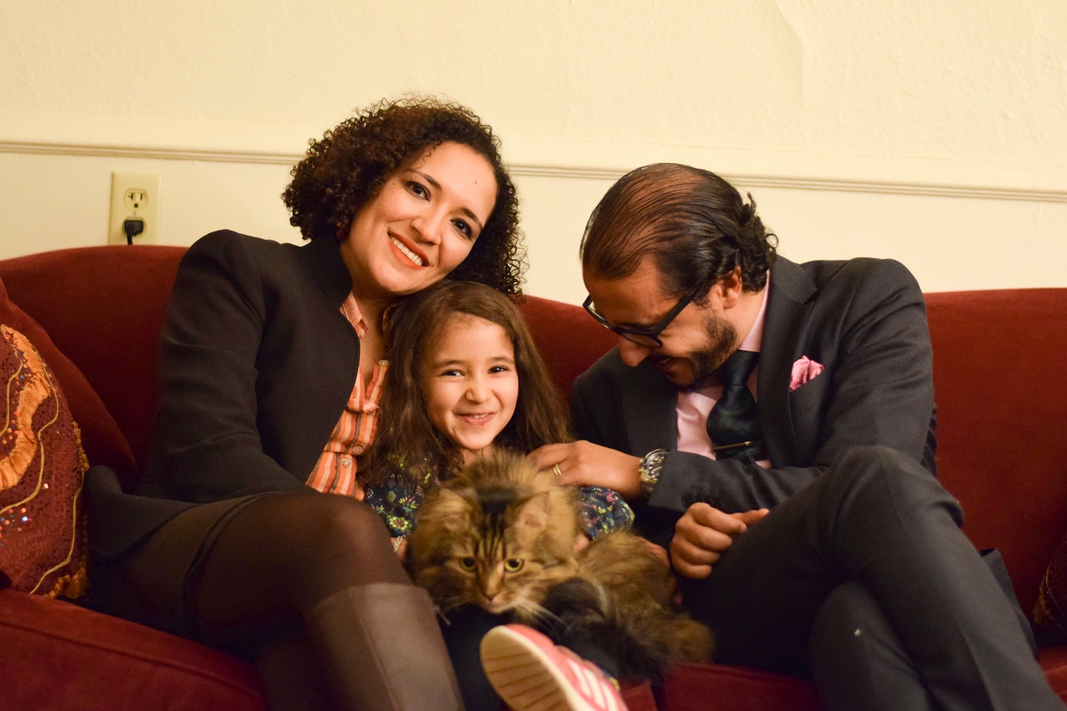 From left to right: Professor Soha Bayoumi, their daughter Carmen holding their cat Jesse, and Professor Ahmed Ragab, in their home living room in Kirkland House.