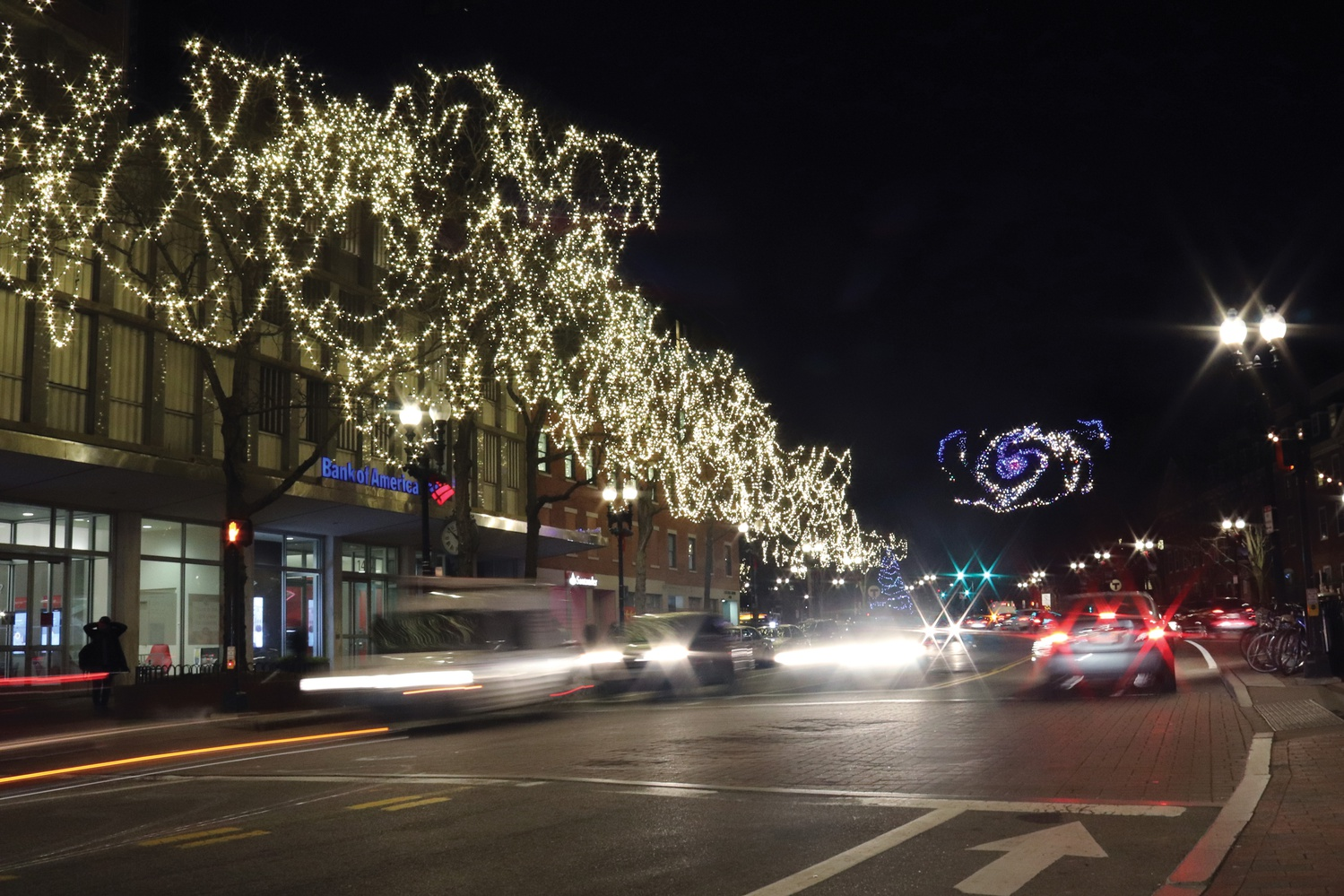 The holiday lights shine brightly in Harvard Square as snow gently falls in the afternoon darkness.