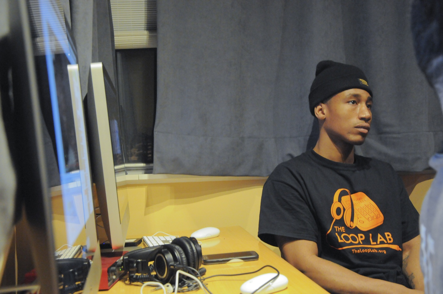 Tevin Charles, a resident of an underrepresented neighborhood in Cambridge called the Port, is focused on preparing for his final project at the Loop Lab by utilizing professional recording equipment.